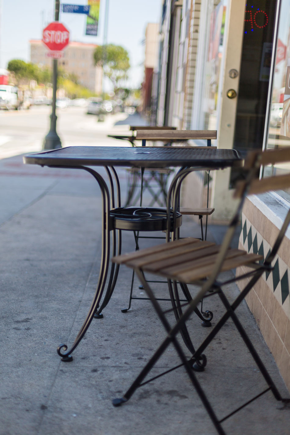 cafe tables and chairs Architecture Building Building Exterior Cafe Cafe Entrance Chairs City Close-up Day Focus On Foreground Metal Tables Morning No People Outdoors Patio Roads Shade Shaded Shallow Depth Of Field Street Tables Town Urban Windows