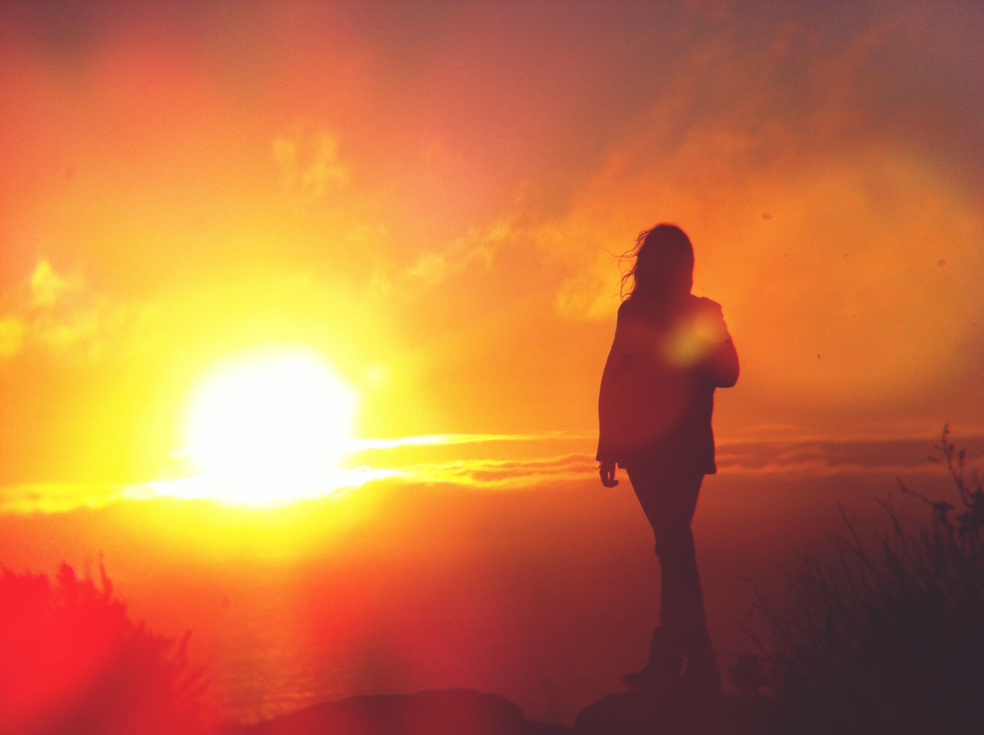sunset, sun, silhouette, orange color, lifestyles, leisure activity, sky, standing, men, full length, sunlight, beauty in nature, rear view, sunbeam, scenics, nature, lens flare, tranquility