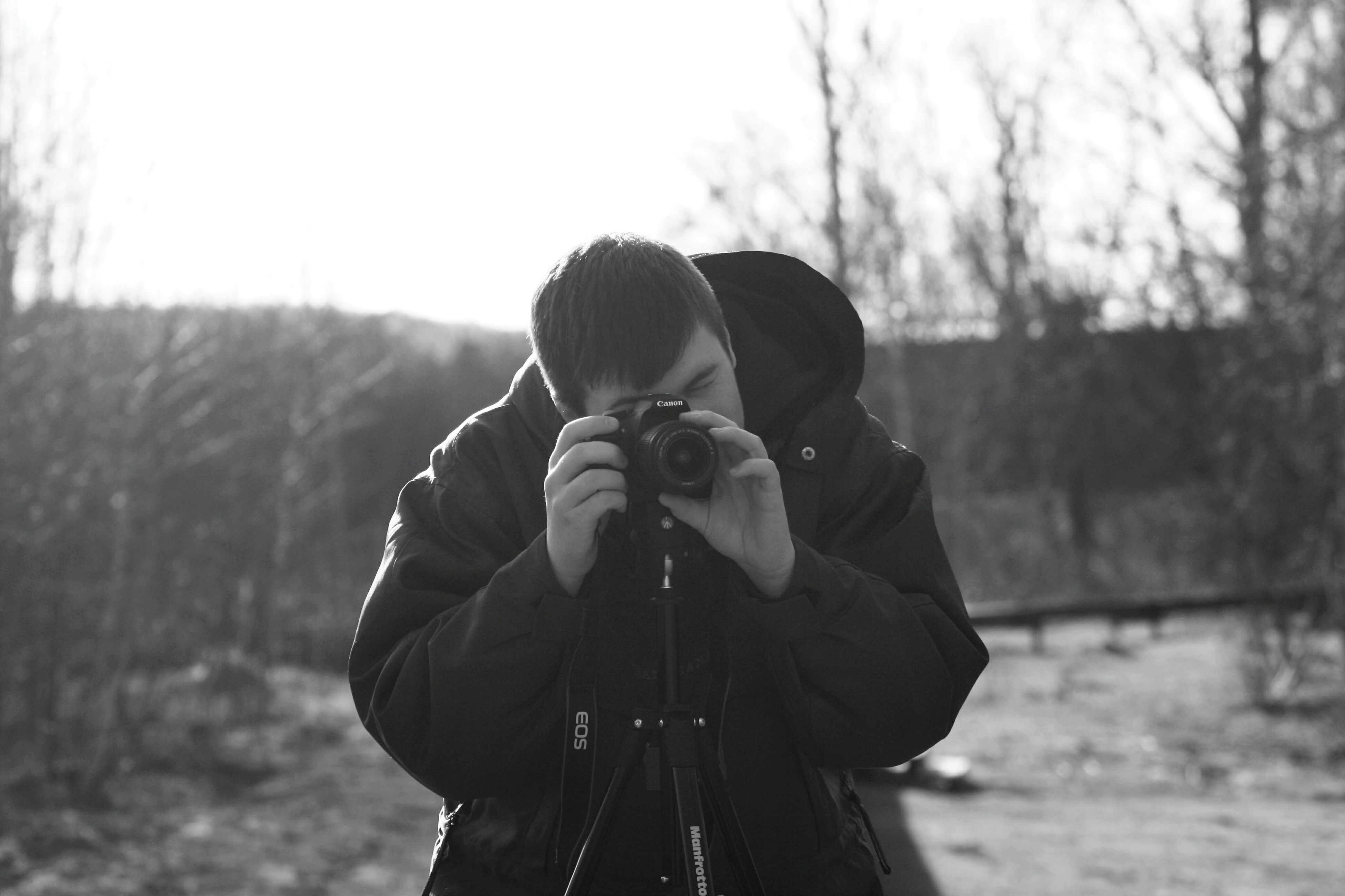 lifestyles, rear view, leisure activity, focus on foreground, men, holding, casual clothing, photographing, photography themes, standing, waist up, camera - photographic equipment, three quarter length, person, clear sky, hat, warm clothing