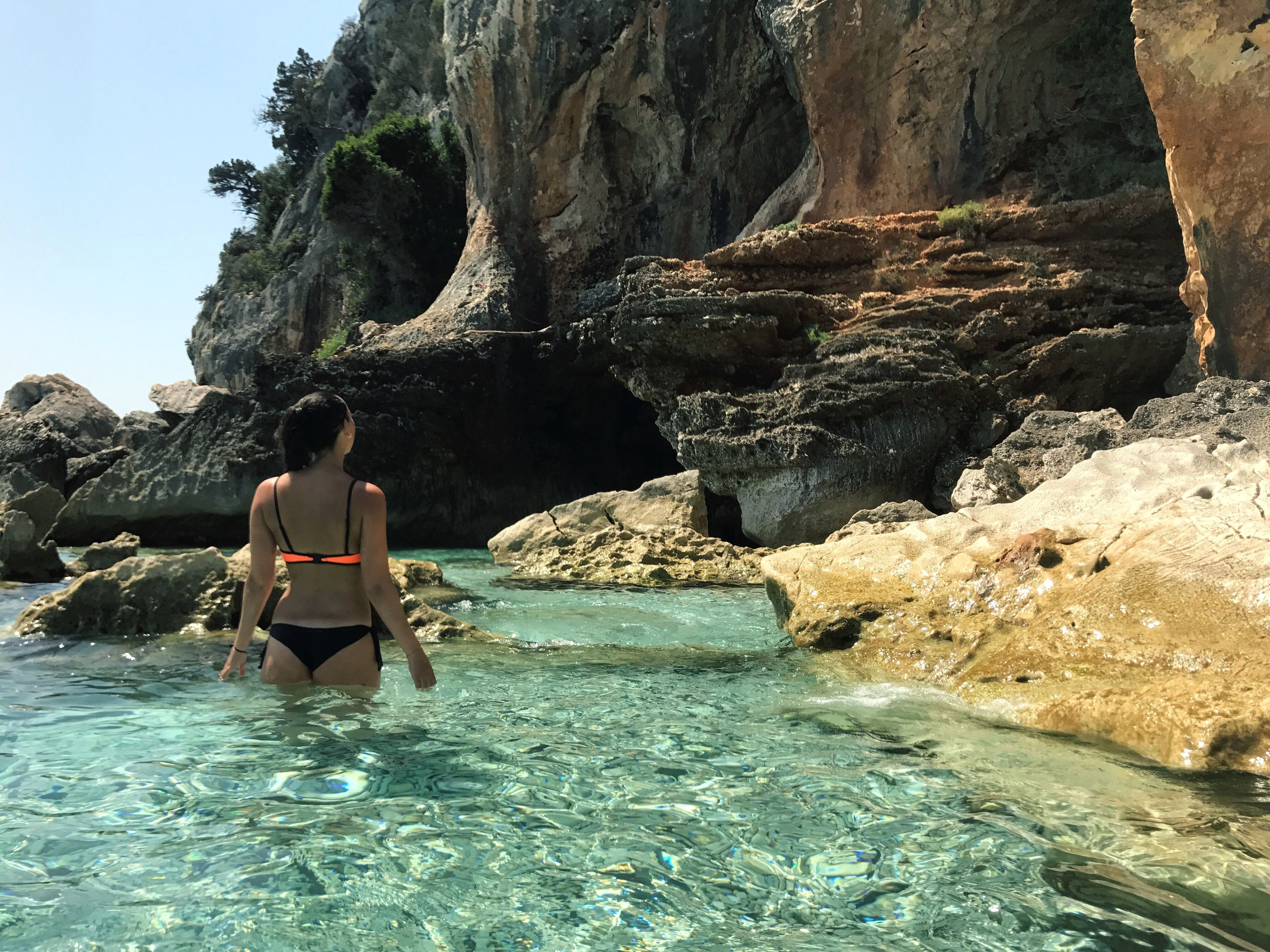 rock - object, rock formation, real people, water, rear view, leisure activity, beauty in nature, nature, one person, young adult, young women, lifestyles, bikini, full length, scenics, vacations, waterfront, day, sea, adventure, outdoors, cave, women, tree, sky