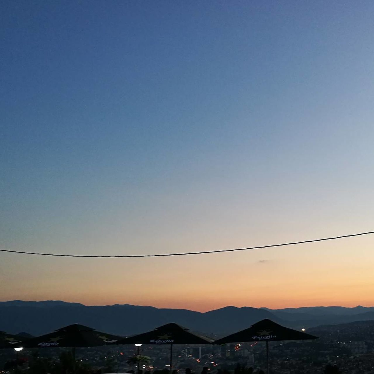 mountain, sunset, silhouette, beauty in nature, nature, copy space, no people, cable, clear sky, outdoors, scenics, tranquil scene, mountain range, sky, landscape, blue, tranquility, electricity, building exterior, architecture, day