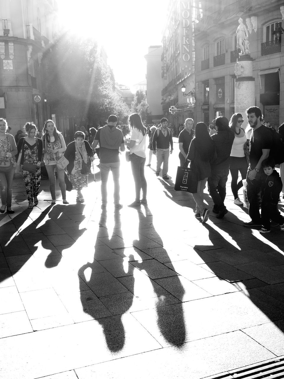 large group of people, sunlight, real people, shadow, building exterior, men, built structure, day, architecture, women, lifestyles, leisure activity, outdoors, city life, casual clothing, walking, crowd, city, togetherness, musician, people, adult