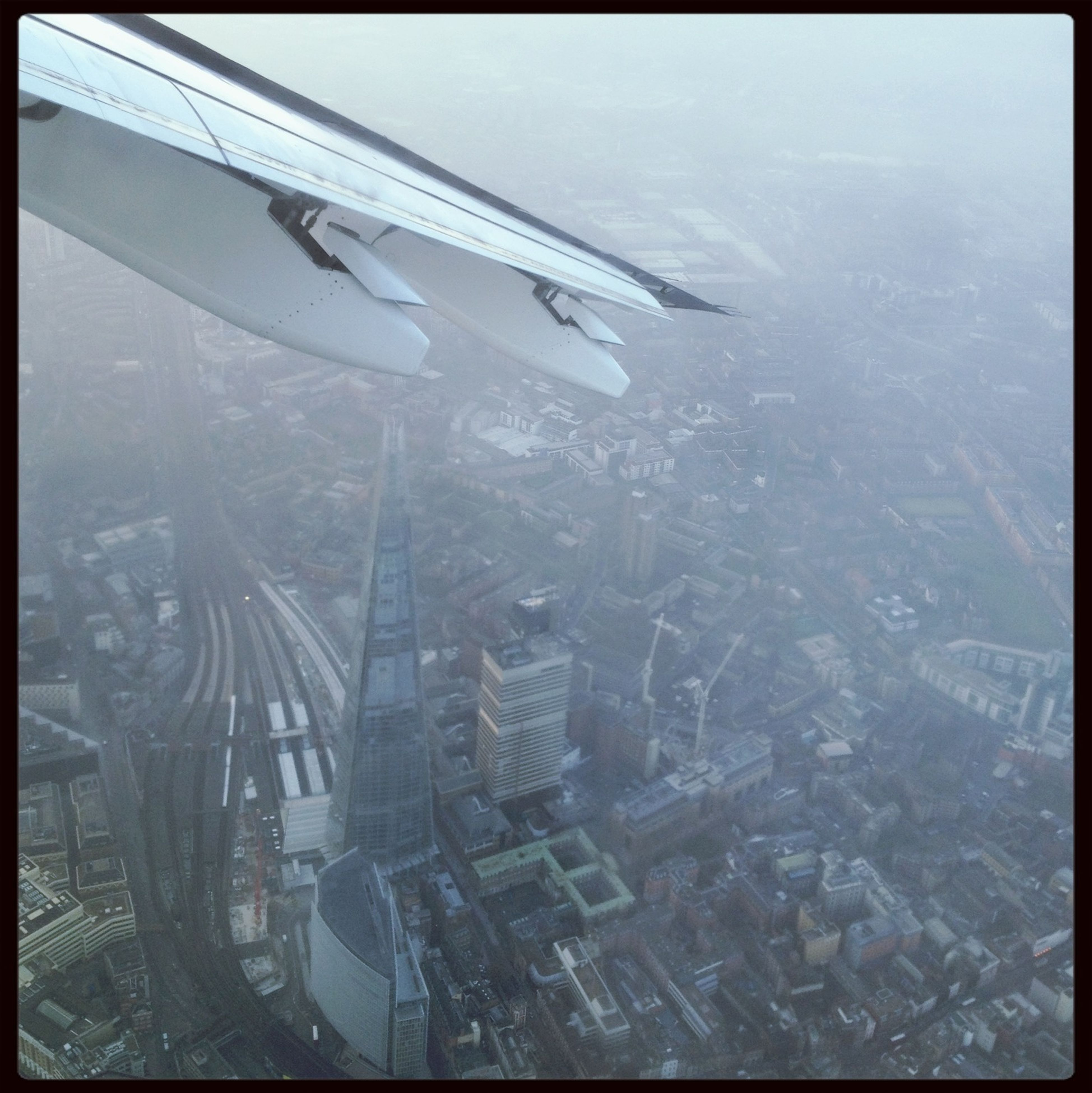 airplane, air vehicle, flying, aerial view, mode of transport, transfer print, transportation, aircraft wing, auto post production filter, part of, mid-air, travel, cropped, water, high angle view, journey, day, on the move, city, landscape