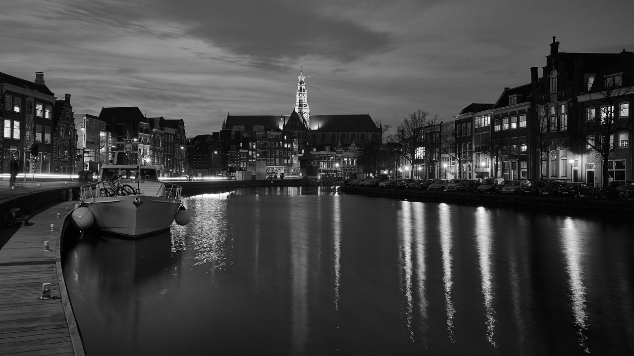 Illuminated Grote Kerk With Reflection In Spaarne River Against Sky At Night