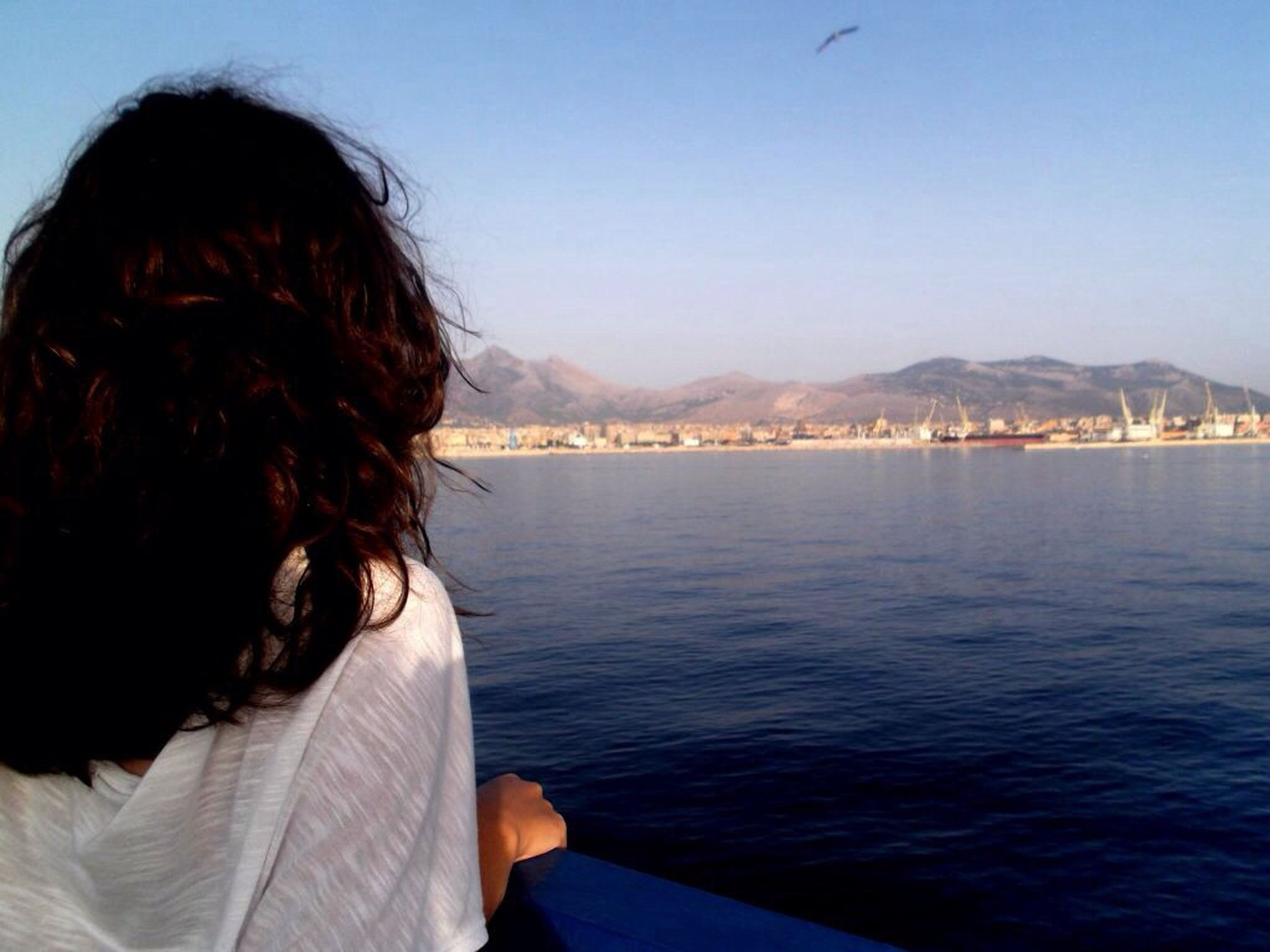 water, mountain, sea, leisure activity, lifestyles, clear sky, mountain range, rear view, scenics, sky, tranquility, nature, person, tranquil scene, beauty in nature, vacations, long hair, beach