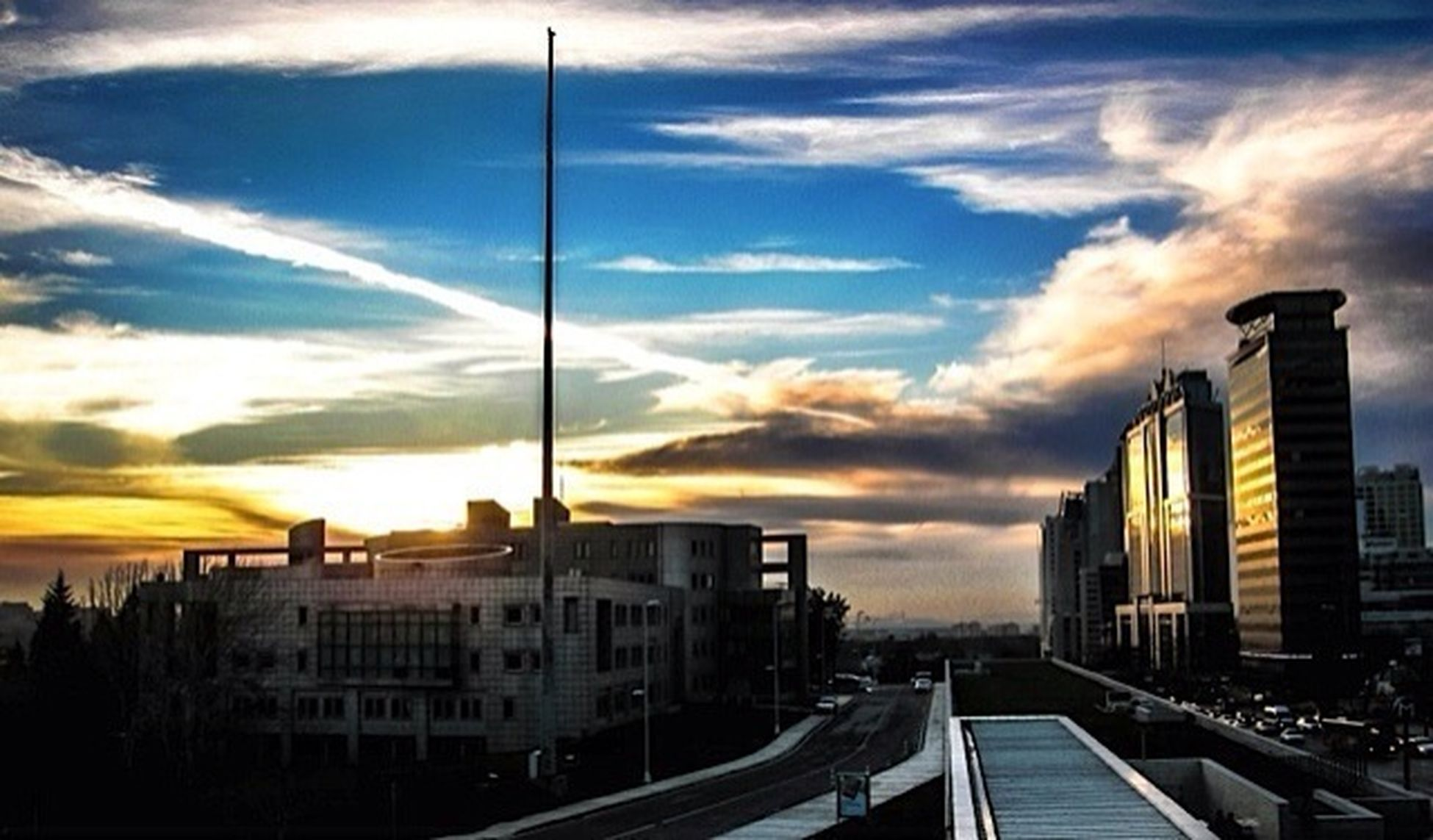 architecture, sky, built structure, building exterior, sunset, cloud - sky, city, cloud, cloudy, street light, building, railing, outdoors, the way forward, sunlight, orange color, transportation, residential structure, residential building, water