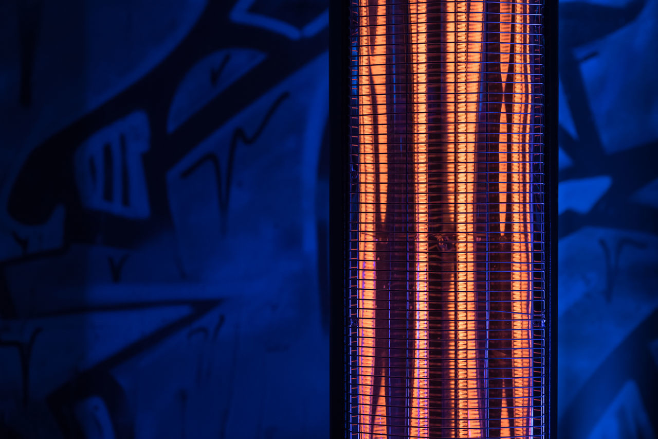 Close-Up Of Radiant Heater Against Blue Wall
