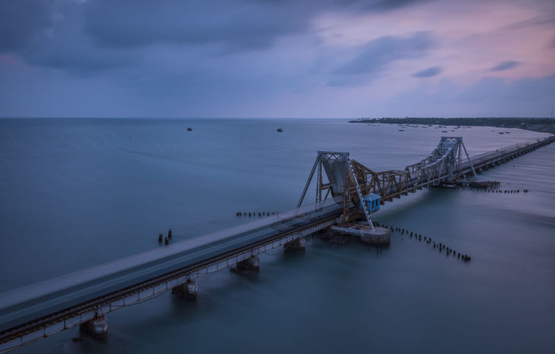 A train crossing the panban bridge before sunrise. I woke up early to watch this beautiful scene from a road bridge adjacent to this railbridge. This is a very old cantilever bridge and indias first sea bridge. It is the longest railway bridge in india untill 2010 Bridge Bridge - Man Made Structure Clear Sky Connection Engineering Long Exposure Ocean Outdoors Panban Bridge Rail Railway Rameshwaram Sea Suspension Bridge Train Traveling Water Waterfront Blue Wave Original Experiences Eyeemphoto The Great Outdoors - 2016 EyeEm Awards The Great Outdoors - 2017 EyeEm Awards Neighborhood Map