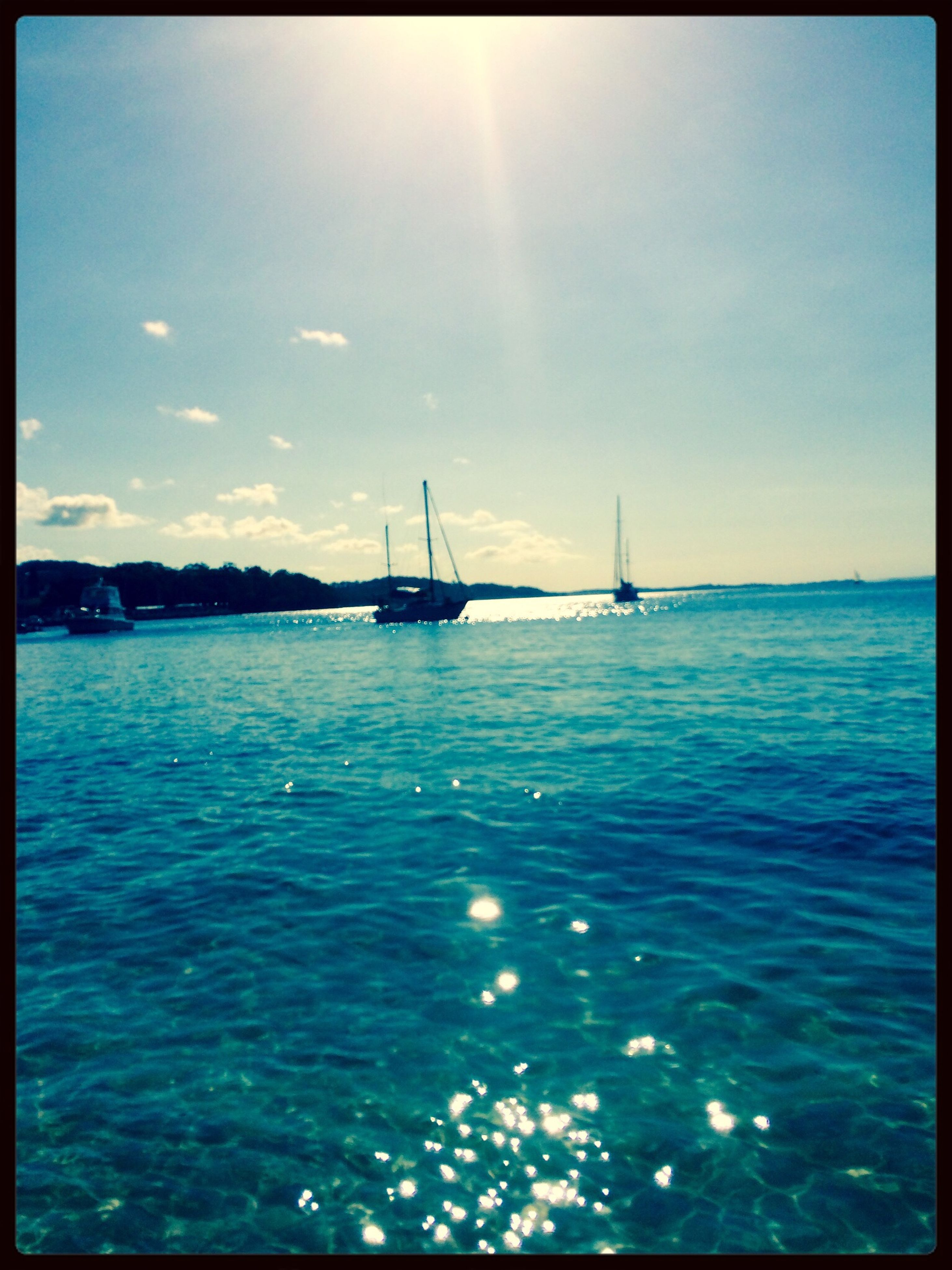 water, sea, nautical vessel, transportation, mode of transport, sky, boat, horizon over water, tranquil scene, sun, tranquility, scenics, sunlight, beauty in nature, blue, waterfront, transfer print, nature, sailboat, sunbeam