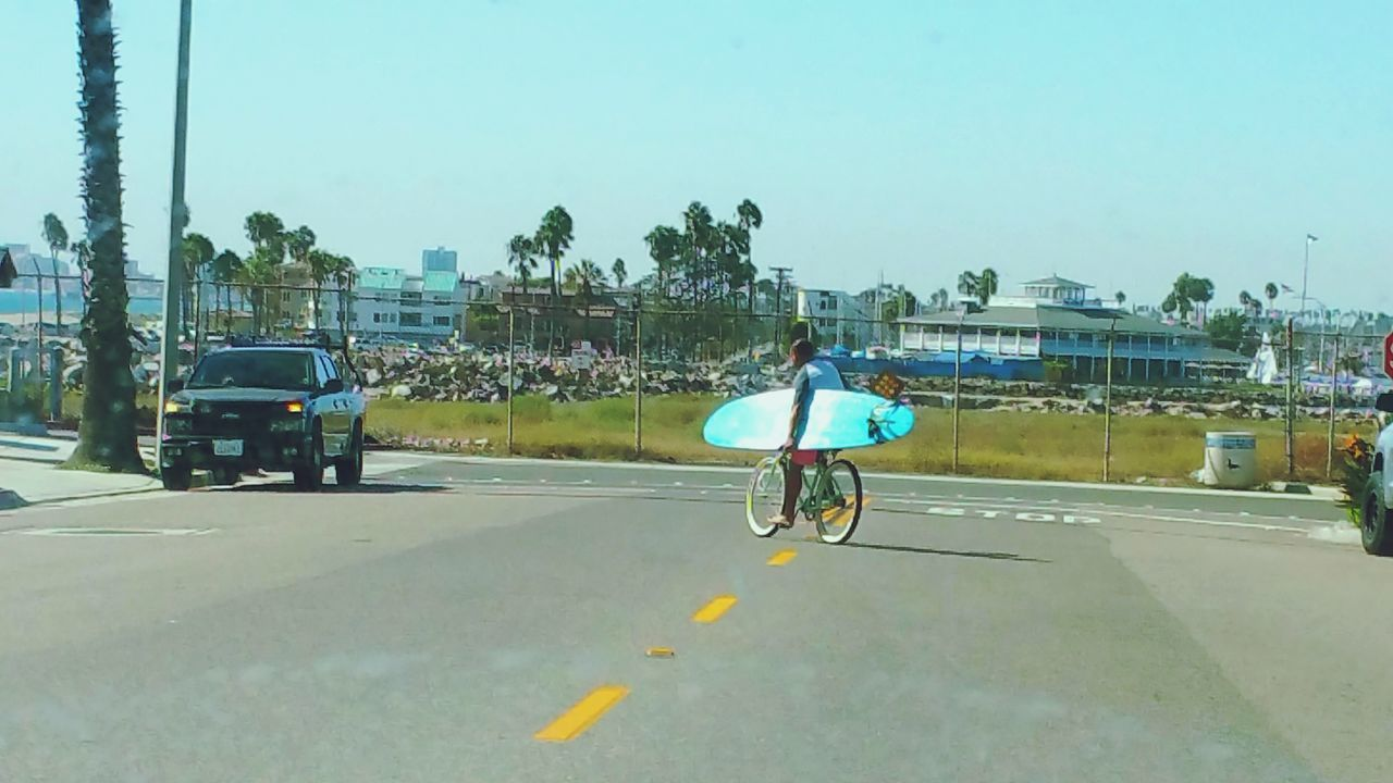 All Roads Lead To The Surf Surfboard Surfers Bicycle To The Beach Bicycle And Surfboard Transportation Mode Of Transport Land Vehicle Person Sunny Palm Trees Street Photography Street Life Check This Out Building Exterior Street People And Places Seal Beach, California Scenics Heading To The Ocean
