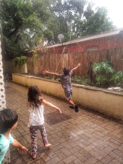 Motion Fun Childhood Summertime Girls Real People Child Boys Outdoors Summer Storm Playing In The Rain Friendship Lifestyles Day Water Rear View