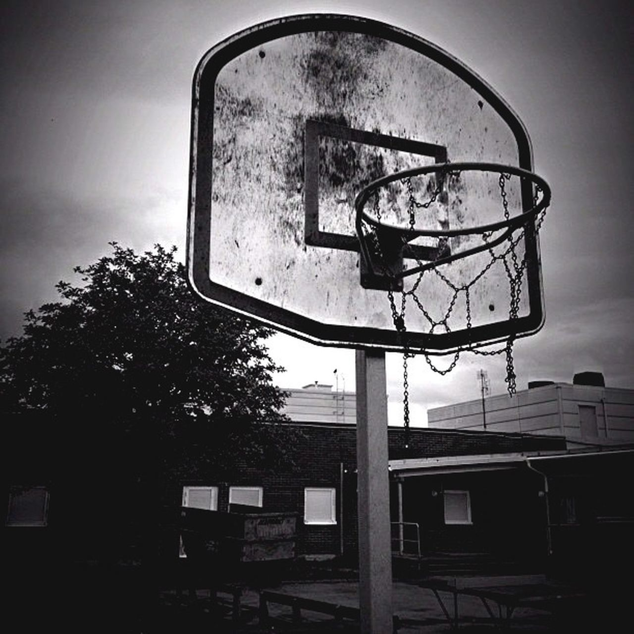 low angle view, built structure, building exterior, architecture, window, tree, sky, technology, electricity, lighting equipment, glass - material, basketball hoop, day, no people, old-fashioned, street light, outdoors, communication, house, time