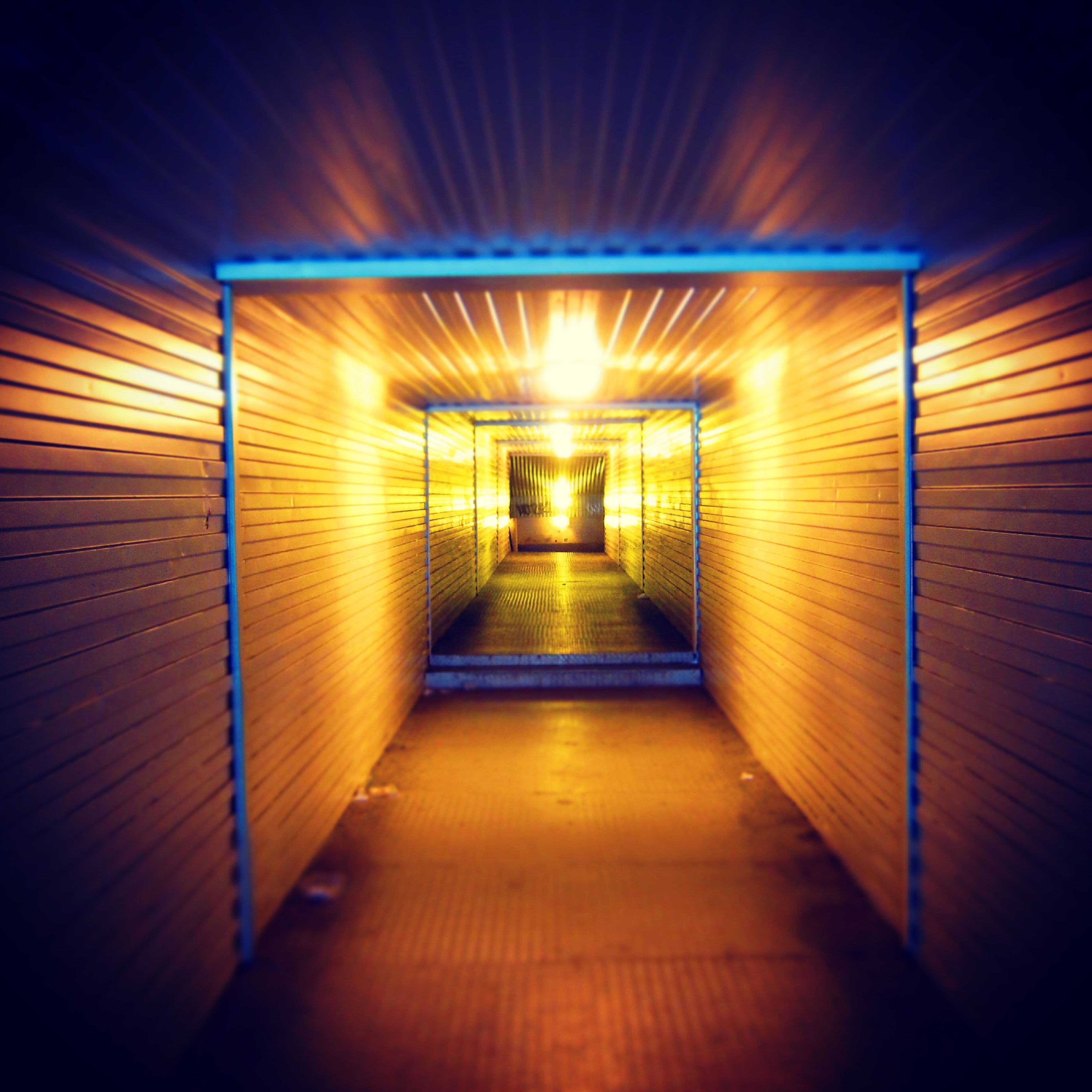 indoors, illuminated, the way forward, empty, lighting equipment, diminishing perspective, light - natural phenomenon, railing, tunnel, wood - material, absence, night, ceiling, vanishing point, steps, wall - building feature, no people, narrow, built structure, flooring