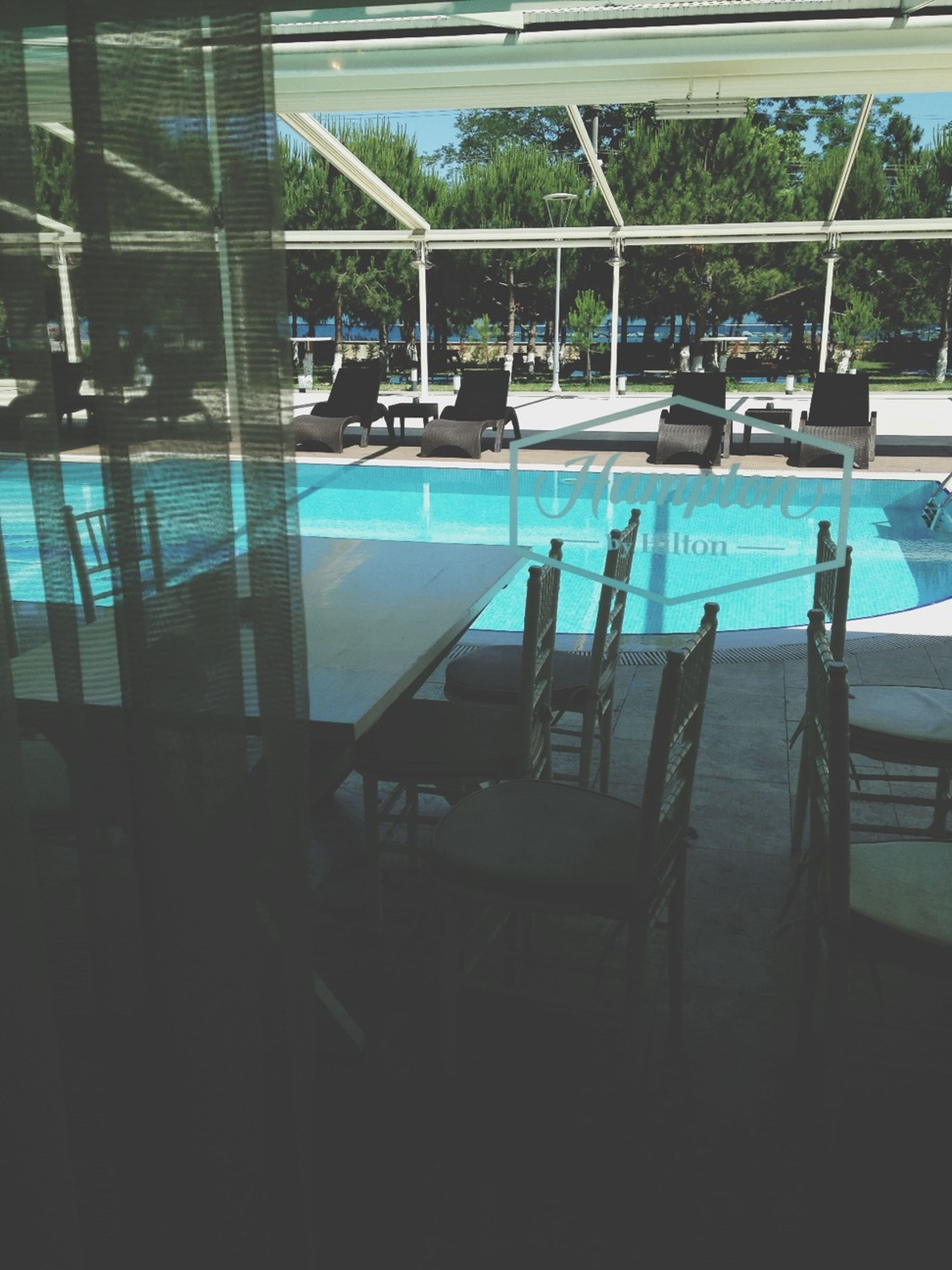 chair, table, empty, blue, absence, indoors, sunlight, built structure, window, swimming pool, day, architecture, glass - material, no people, shadow, reflection, restaurant, railing, water, seat