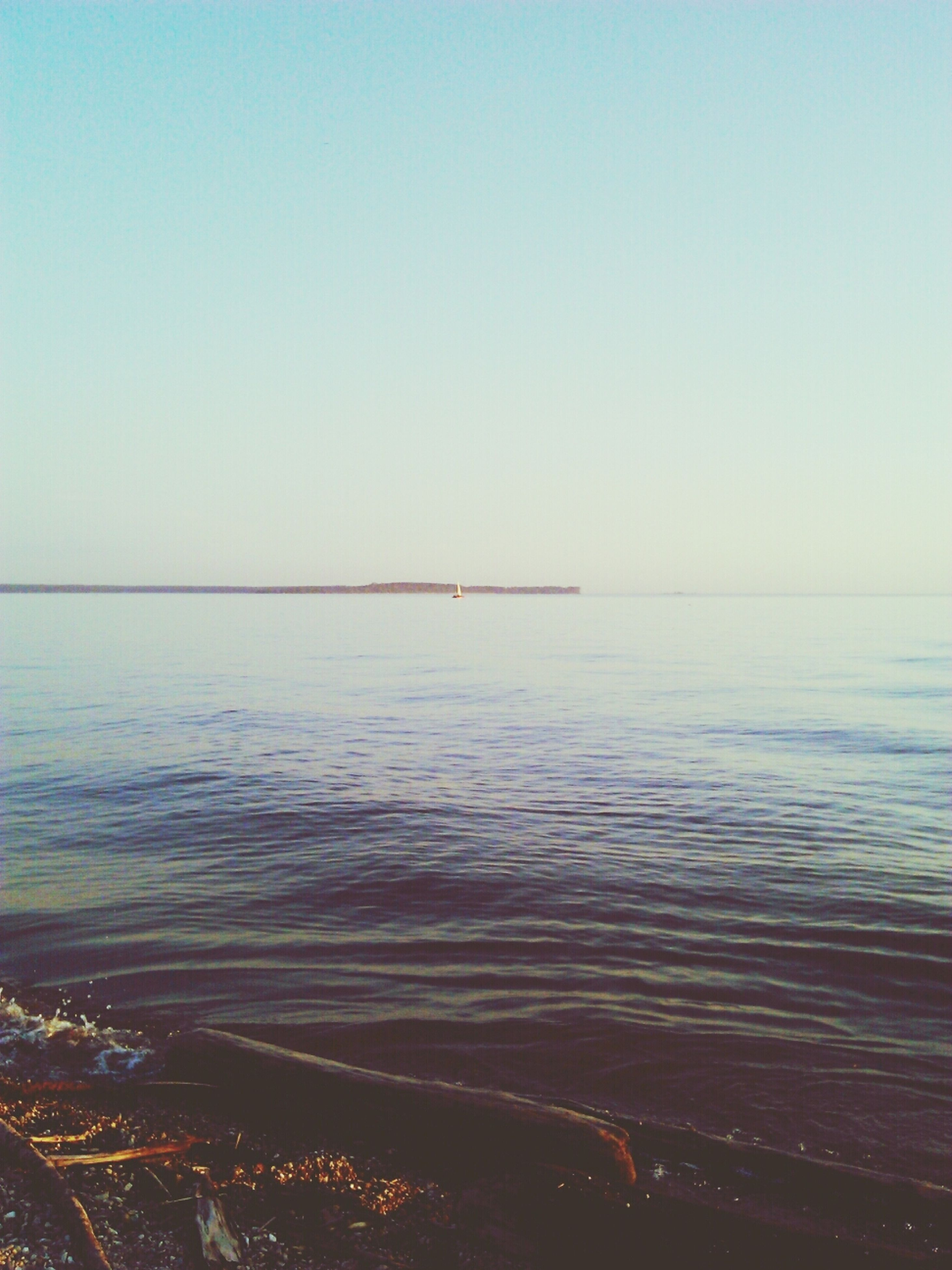 clear sky, water, copy space, sea, tranquil scene, scenics, tranquility, beauty in nature, horizon over water, nature, blue, idyllic, outdoors, beach, sky, no people, calm, remote, non-urban scene, shore