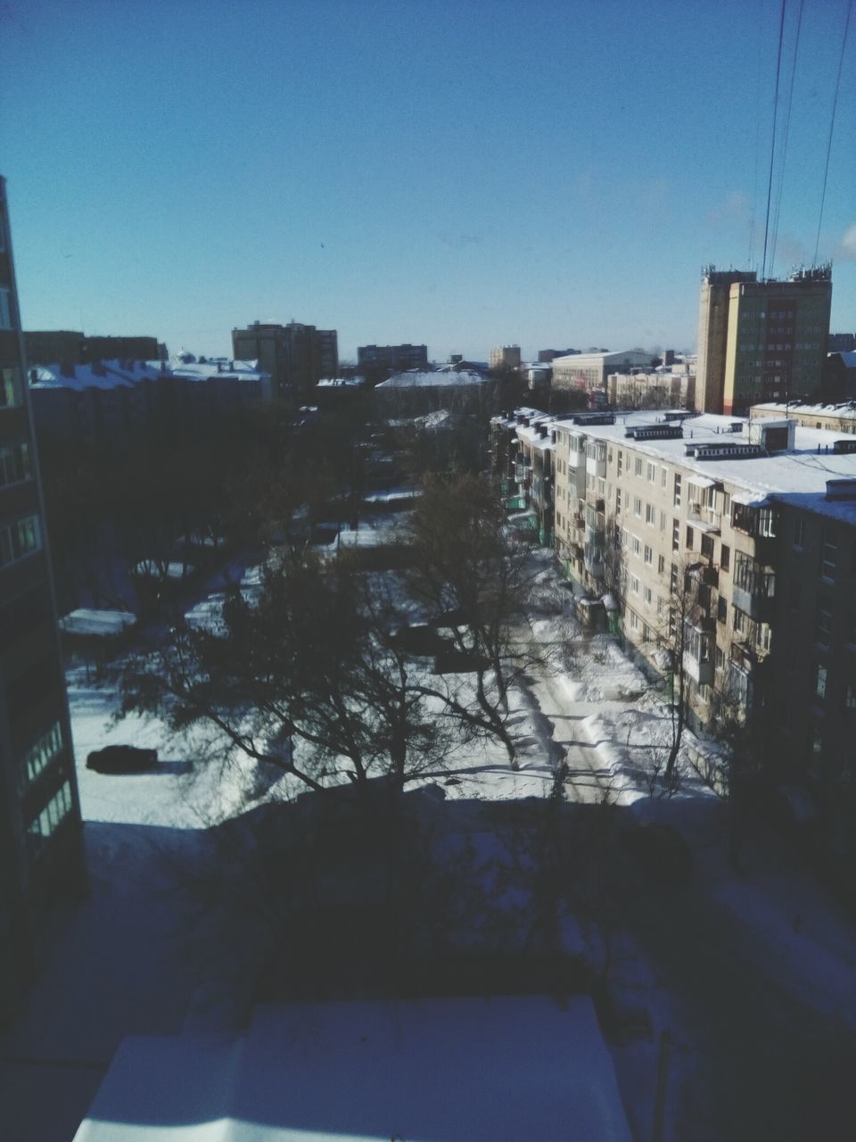 architecture, building exterior, city, clear sky, cityscape, no people, winter, built structure, snow, outdoors, day, nature, sky