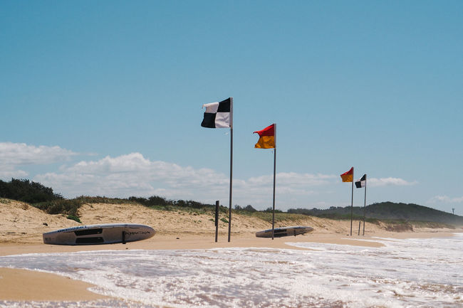 Safety flags on beach Beach Es Flag Flags Flagstaff Horizontal No People Outdoors Safety Sea Sunlight Sunny Surfboard Travel Destinations