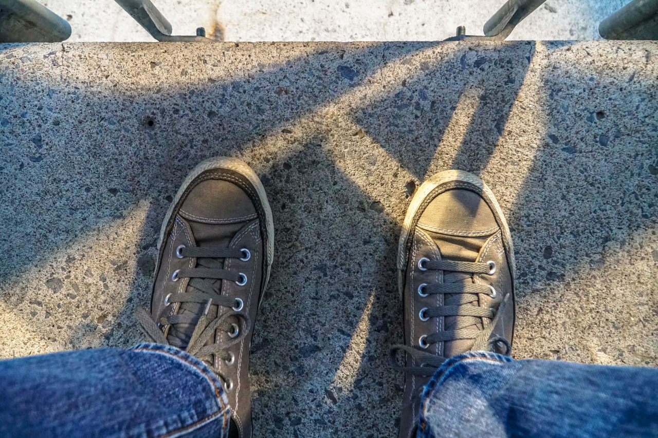 shoe, low section, high angle view, personal perspective, standing, pair, human leg, canvas shoe, real people, day, directly above, outdoors, human body part, one person, close-up, people