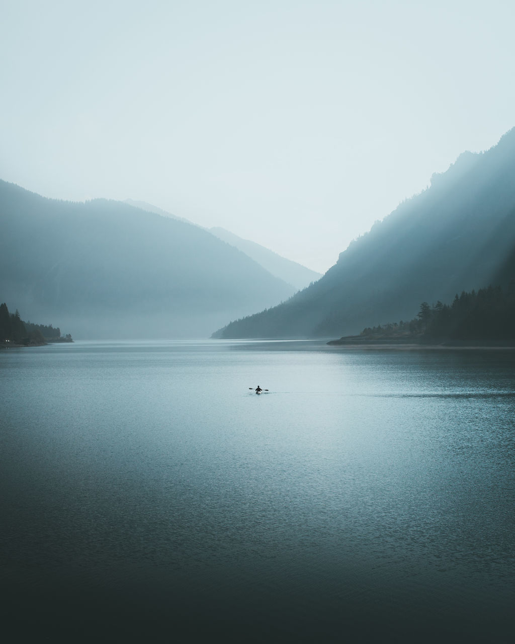 tranquil scene, mountain, scenics, water, nature, beauty in nature, tranquility, lake, outdoors, waterfront, idyllic, mountain range, day, no people, fog, sky