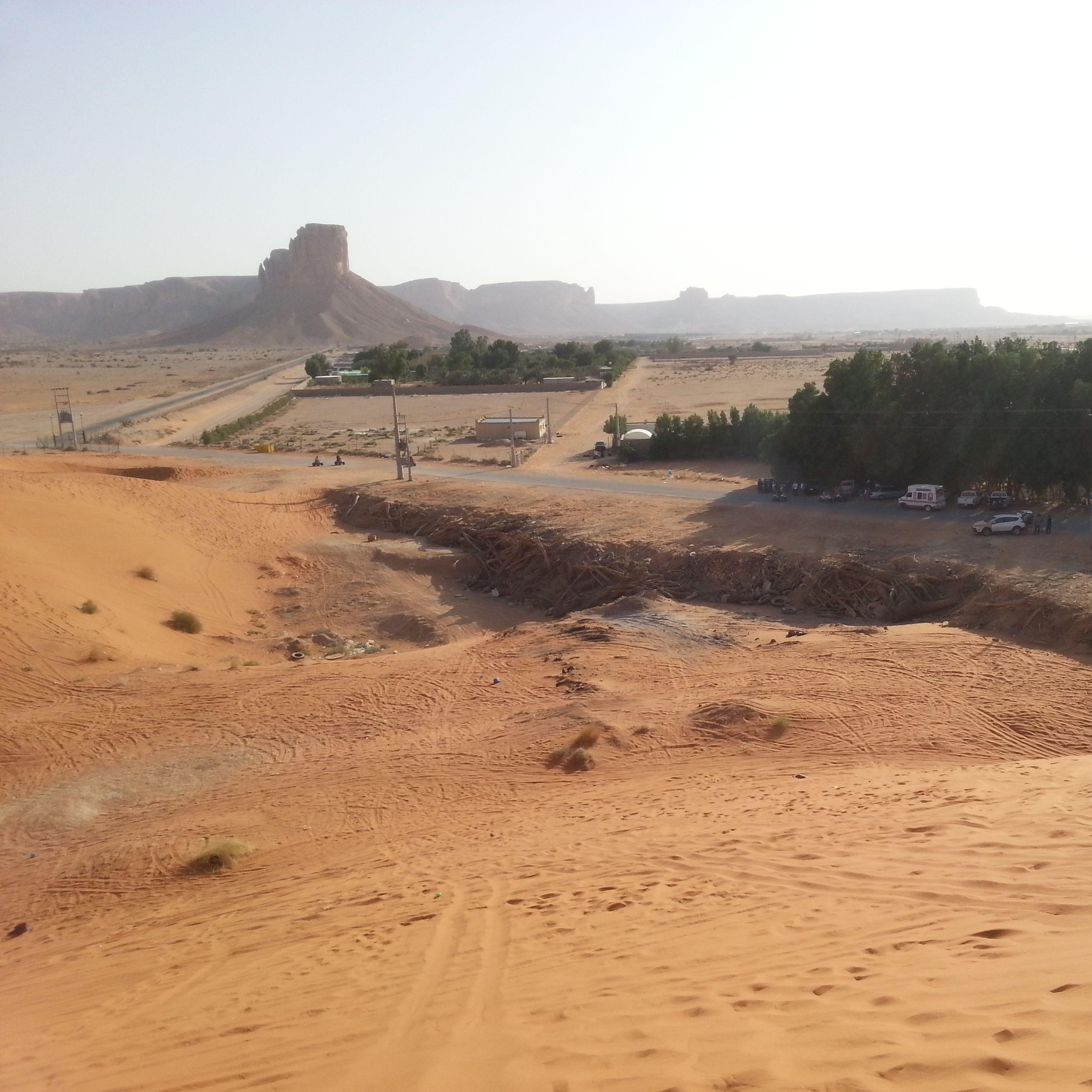 sand, desert, arid climate, clear sky, landscape, sand dune, tranquil scene, tranquility, scenics, nature, barren, mountain, beauty in nature, remote, arid landscape, non-urban scene, dirt road, sunlight, beach, incidental people