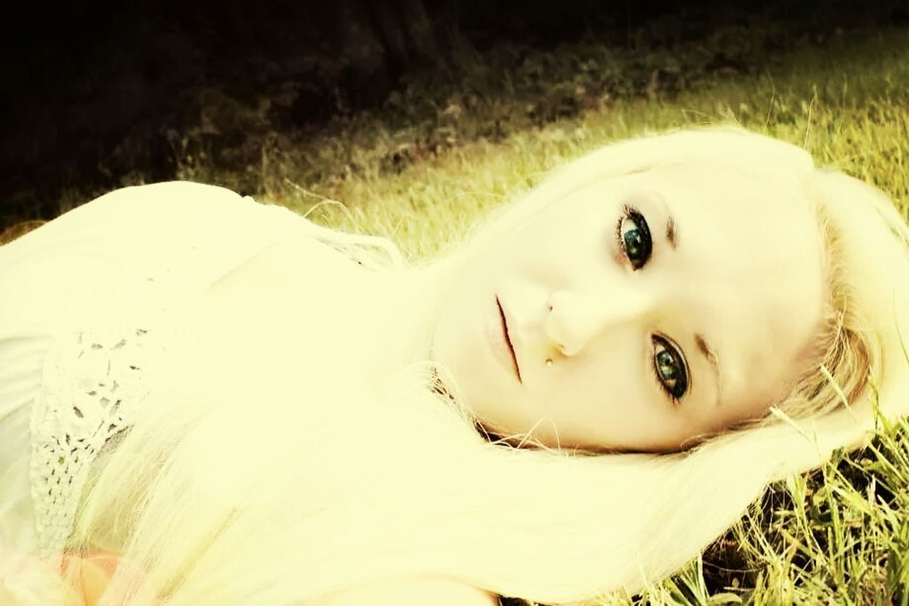 Side view portrait of young woman lying on grass at park