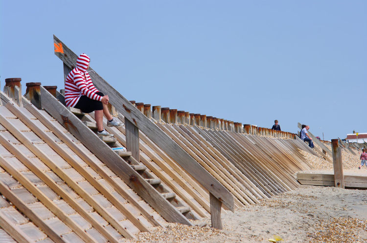 A woman in a stripy top sits at the top of some steps - there is a big arrow behind her on the handrail which points at her Arrow Beach Blue Sky Day Relaxed Sea Defences Seated Steps Striped Hoodie Watching Woman Telling Stories Differently