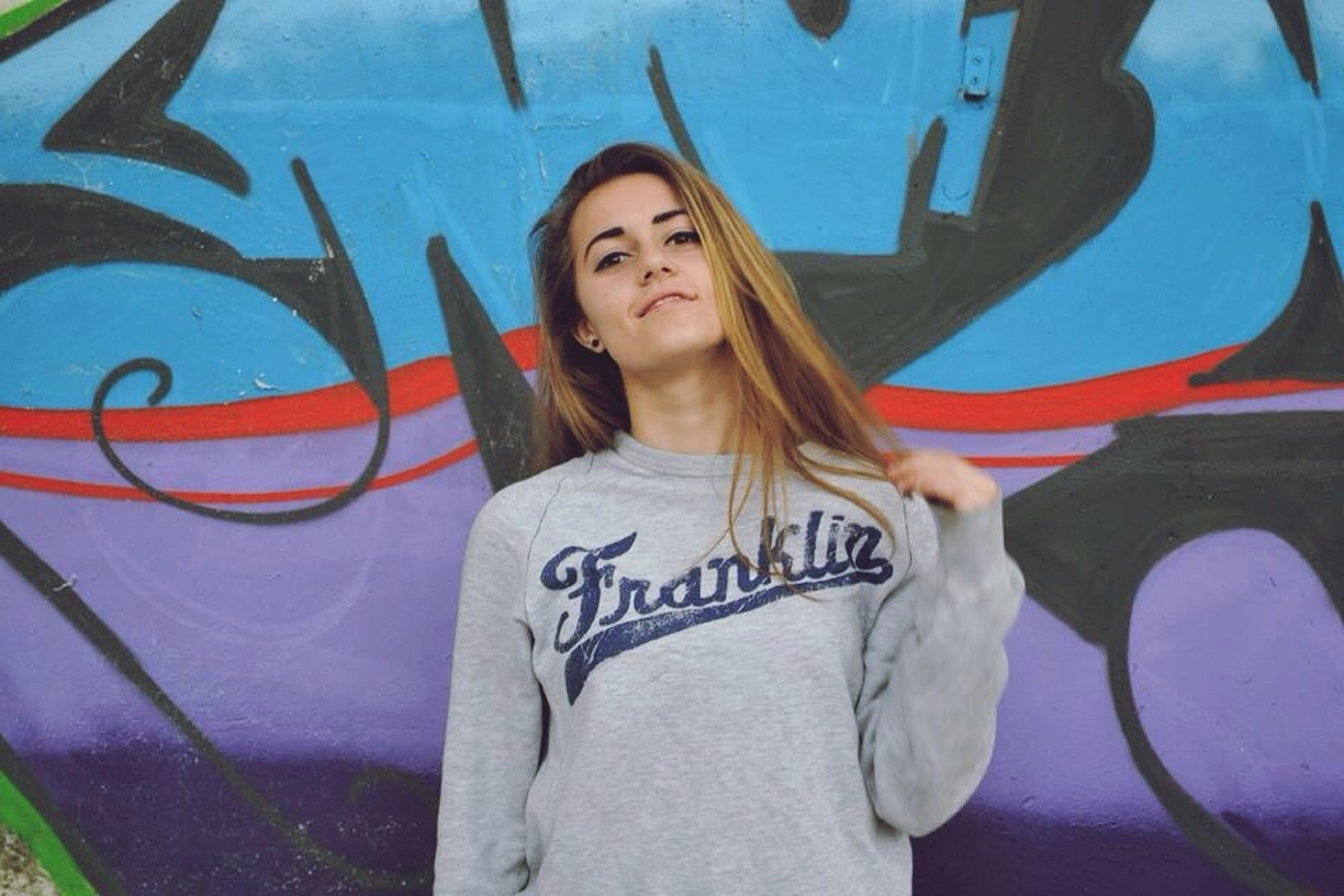 lifestyles, young adult, leisure activity, casual clothing, young women, person, standing, graffiti, three quarter length, looking at camera, long hair, portrait, waist up, front view, day, wall - building feature, outdoors