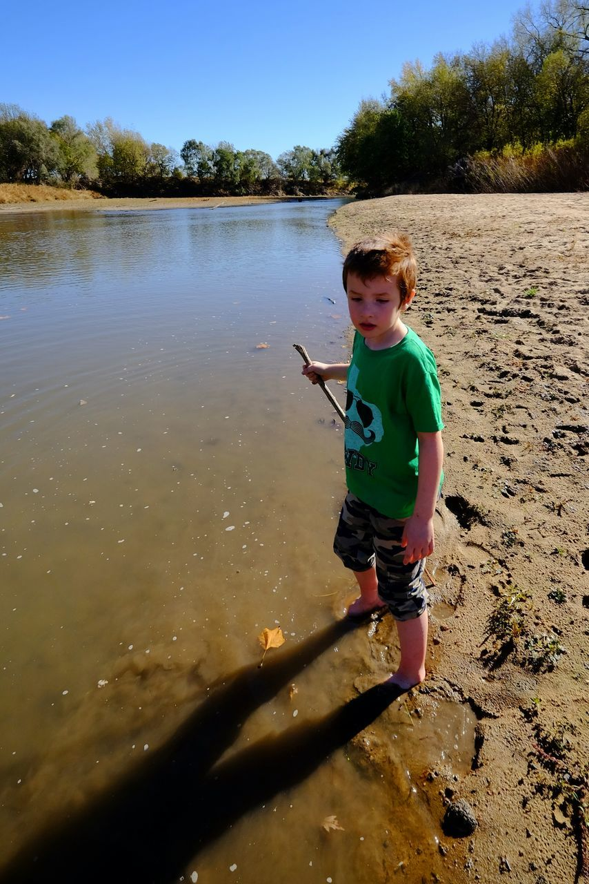 High Angle View Of Boy Holding Stick While Standing At Little Blue River