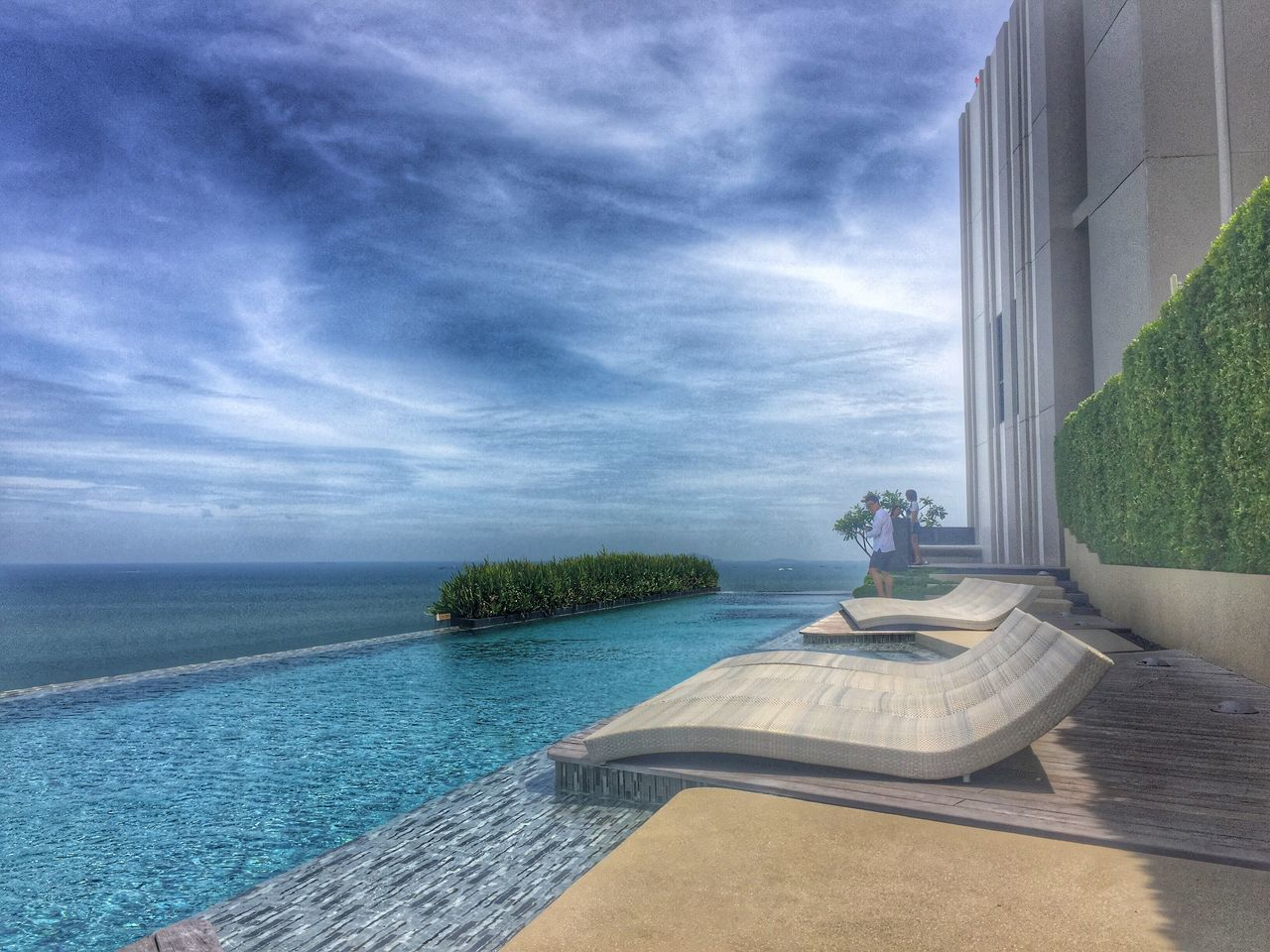 water, swimming pool, sky, architecture, sea, luxury, day, no people, tourist resort, waterfront, built structure, vacations, cloud - sky, horizon over water, modern, outdoors, luxury hotel, scenics, nature, tree, beauty in nature