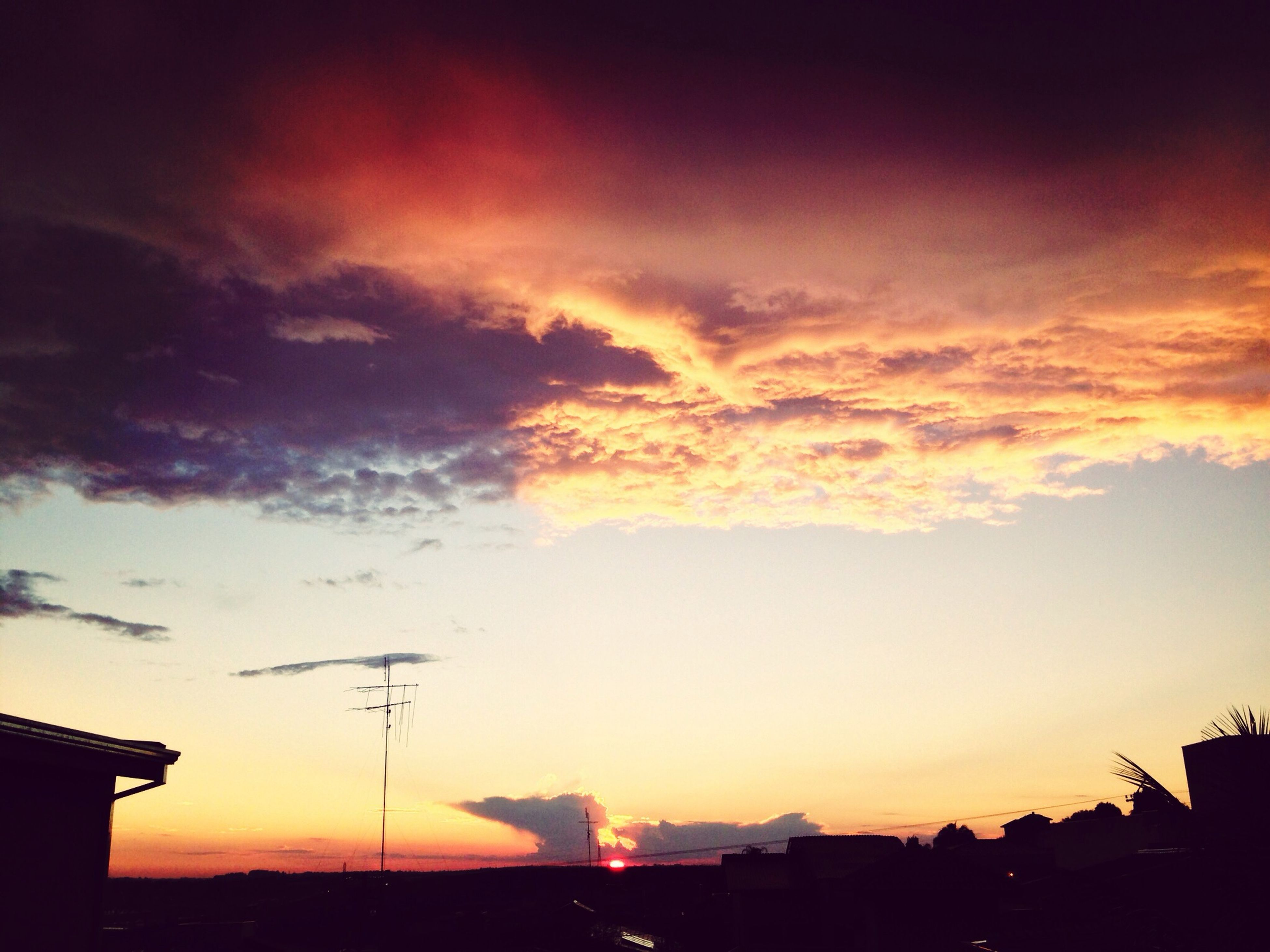 sunset, silhouette, building exterior, architecture, orange color, sky, built structure, cloud - sky, dramatic sky, beauty in nature, low angle view, scenics, house, nature, cloud, city, residential structure, moody sky, outdoors, building