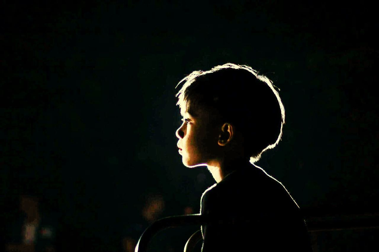 one person, night, headshot, side view, black background, childhood, real people, people, one boy only, outdoors, adult