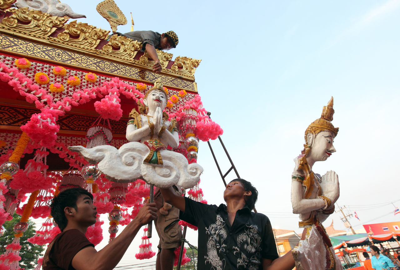 statue, sculpture, low angle view, human representation, real people, architecture, day, outdoors, built structure, building exterior, sky, cloud - sky, lifestyles, togetherness, chinese dragon, city