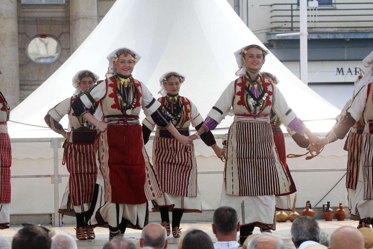 Smiling Traditional Dancers Performing On Stage