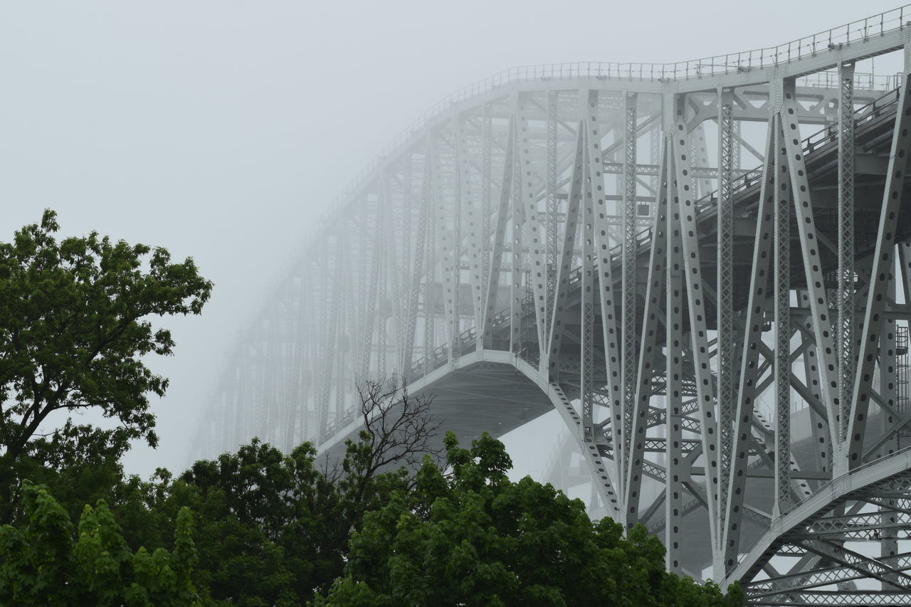 connection, bridge - man made structure, engineering, architecture, built structure, transportation, bridge, arch bridge, railroad bridge, arch, tree, low angle view, suspension bridge, outdoors, river, day, no people, travel destinations, fog, modern, sky, chain bridge, underneath, water, city, nature