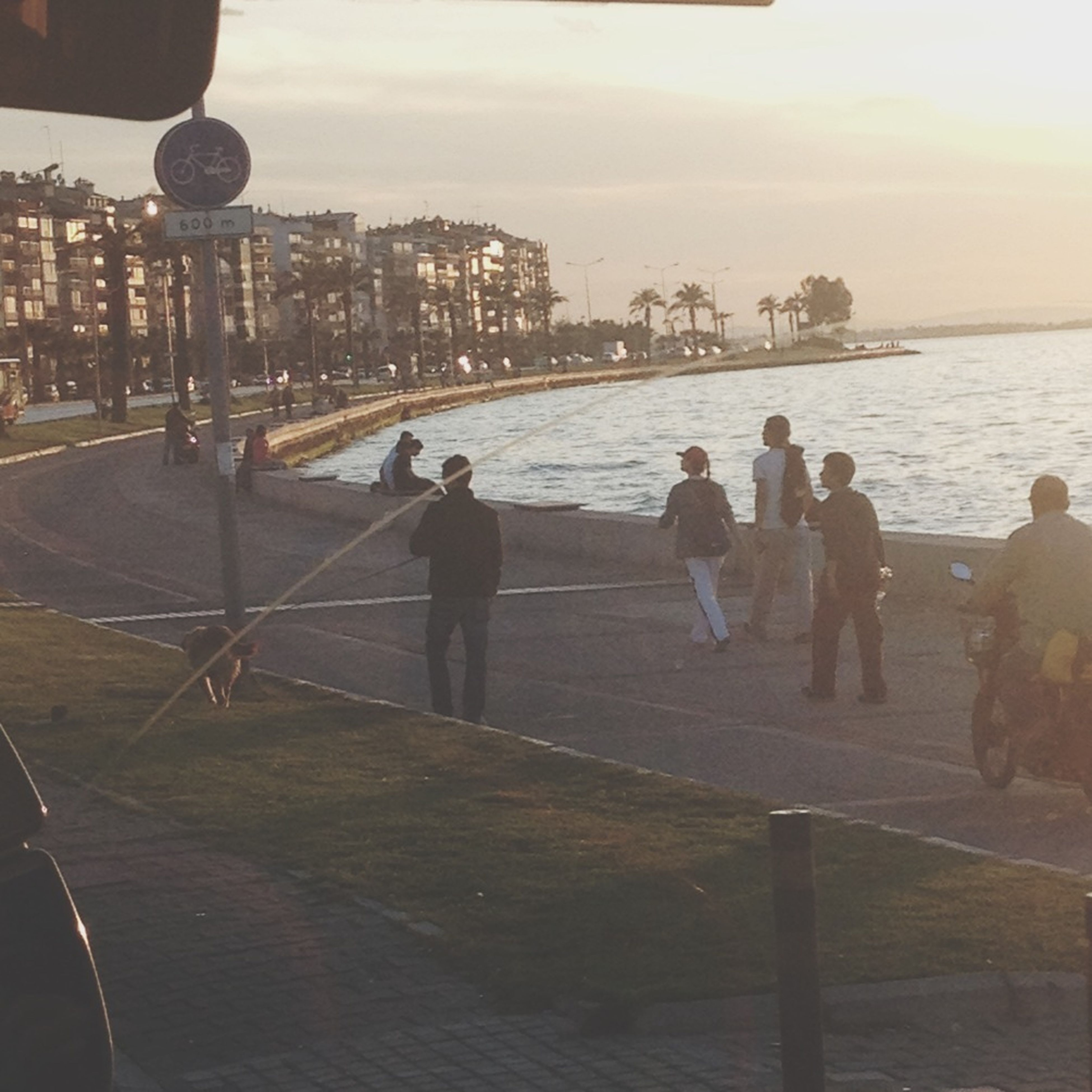 water, lifestyles, sea, men, built structure, architecture, leisure activity, person, building exterior, sky, city, large group of people, railing, walking, standing, city life, rear view, pier, outdoors