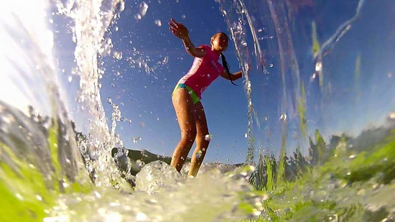 splashing, motion, blue, outdoors, summer, day, low angle view, sky, sunlight, water, fun, spraying, one woman only, nature, adult, people, adults only, full length, clear sky, vacations, happiness, one person, only women, cheerful, beauty in nature, one young woman only, young adult