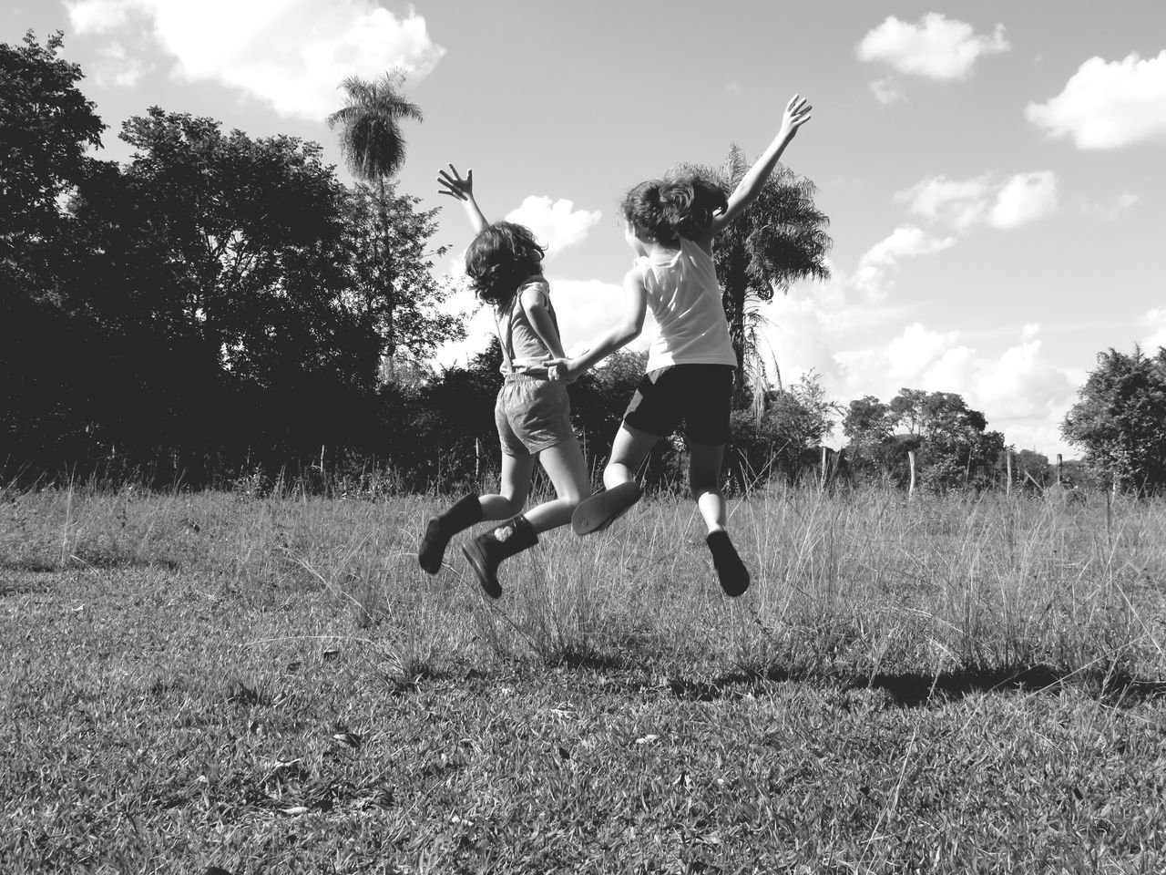 Rear View Of Siblings Jumping On Grassy Field Against Cloudy Sky