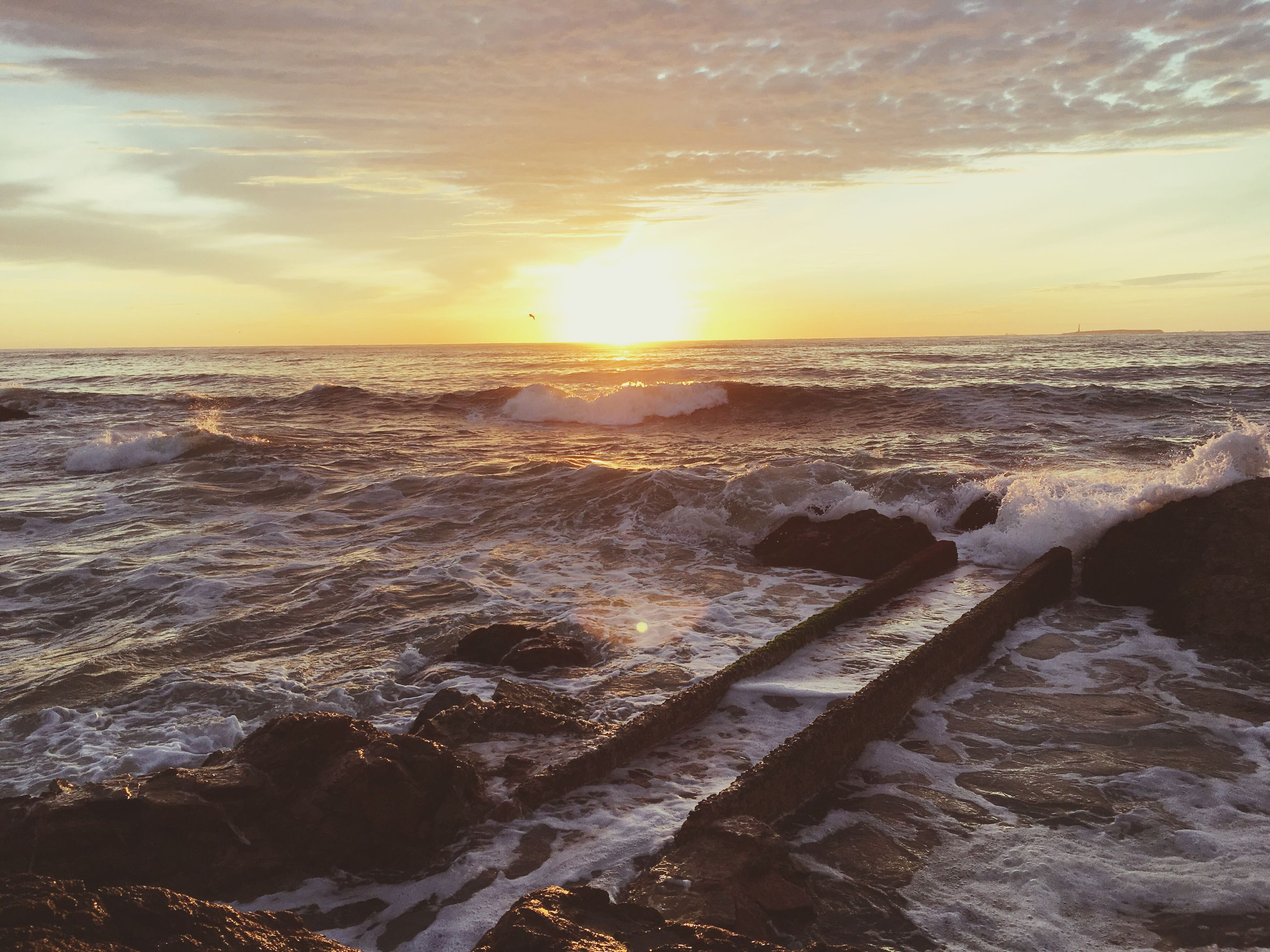 sea, sunset, water, horizon over water, scenics, beauty in nature, beach, wave, tranquil scene, sky, tranquility, shore, nature, orange color, sun, idyllic, rock - object, surf, cloud - sky, sunlight