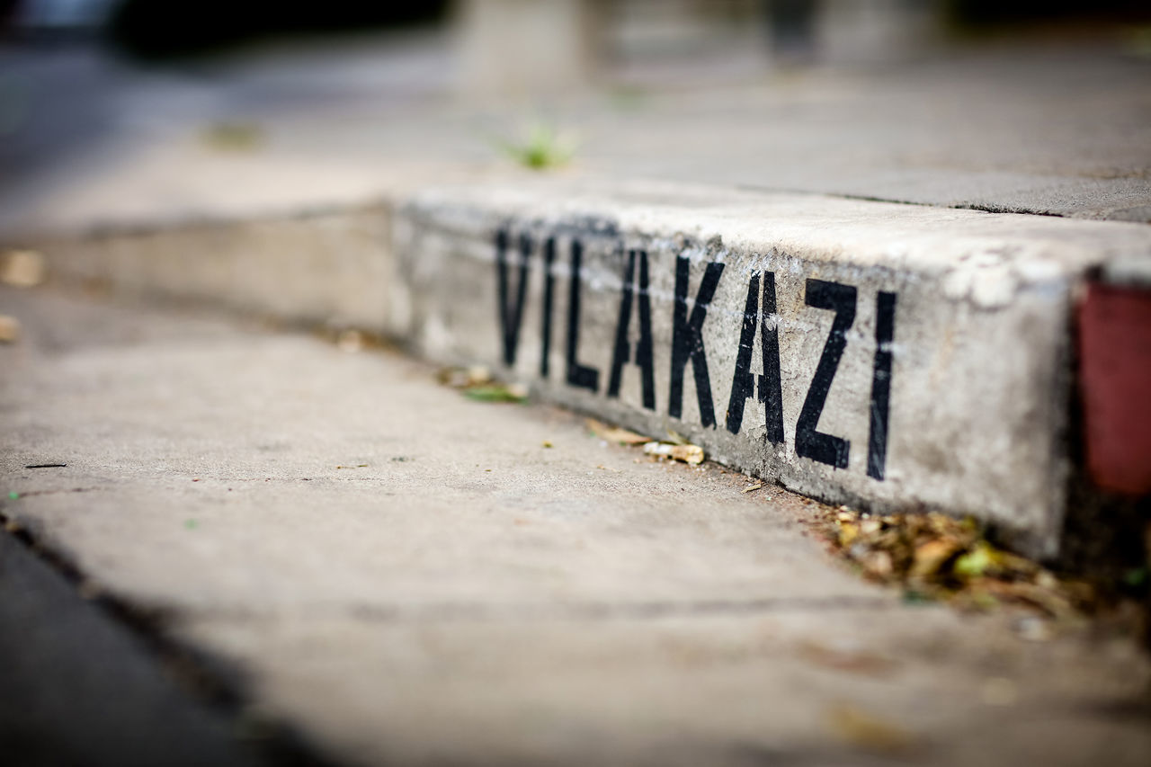selective focus, text, communication, memorial, no people, outdoors, day, retaining wall, close-up, tilt-shift