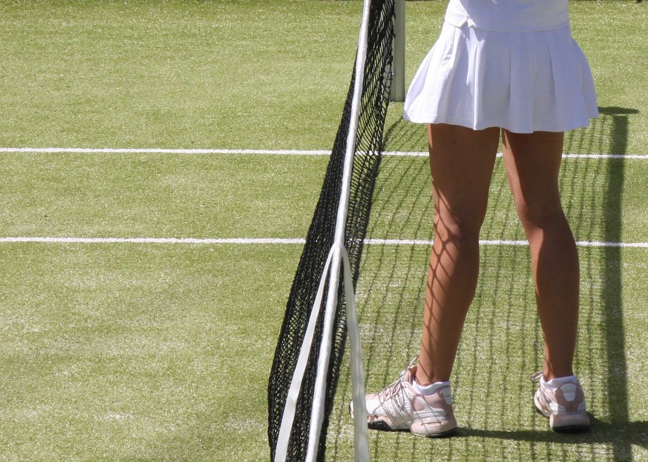 female tennis player in white skirt at net Low Section Green Color Sunny Court Light And Shadow Woman Legs Sport Outdoors White Skirt Standing Net Tennis Court People Leisure Activity Fun Enjoy Tennis Summer Scenics Sports Photography Exceptional Photographs Greenery