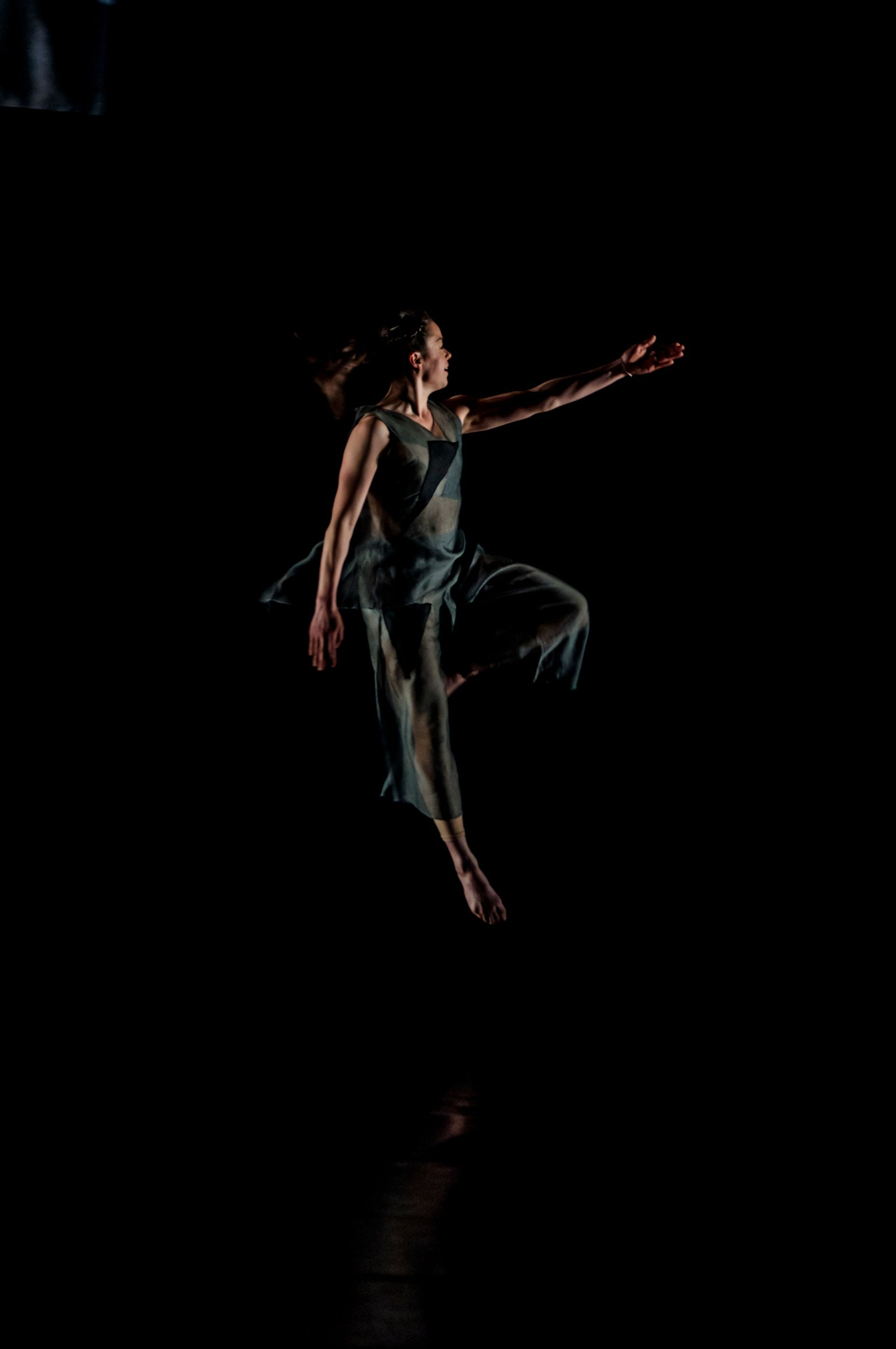 full length, night, lifestyles, leisure activity, studio shot, black background, copy space, motion, young adult, skill, standing, holding, front view, jumping, casual clothing, side view, vitality, performance