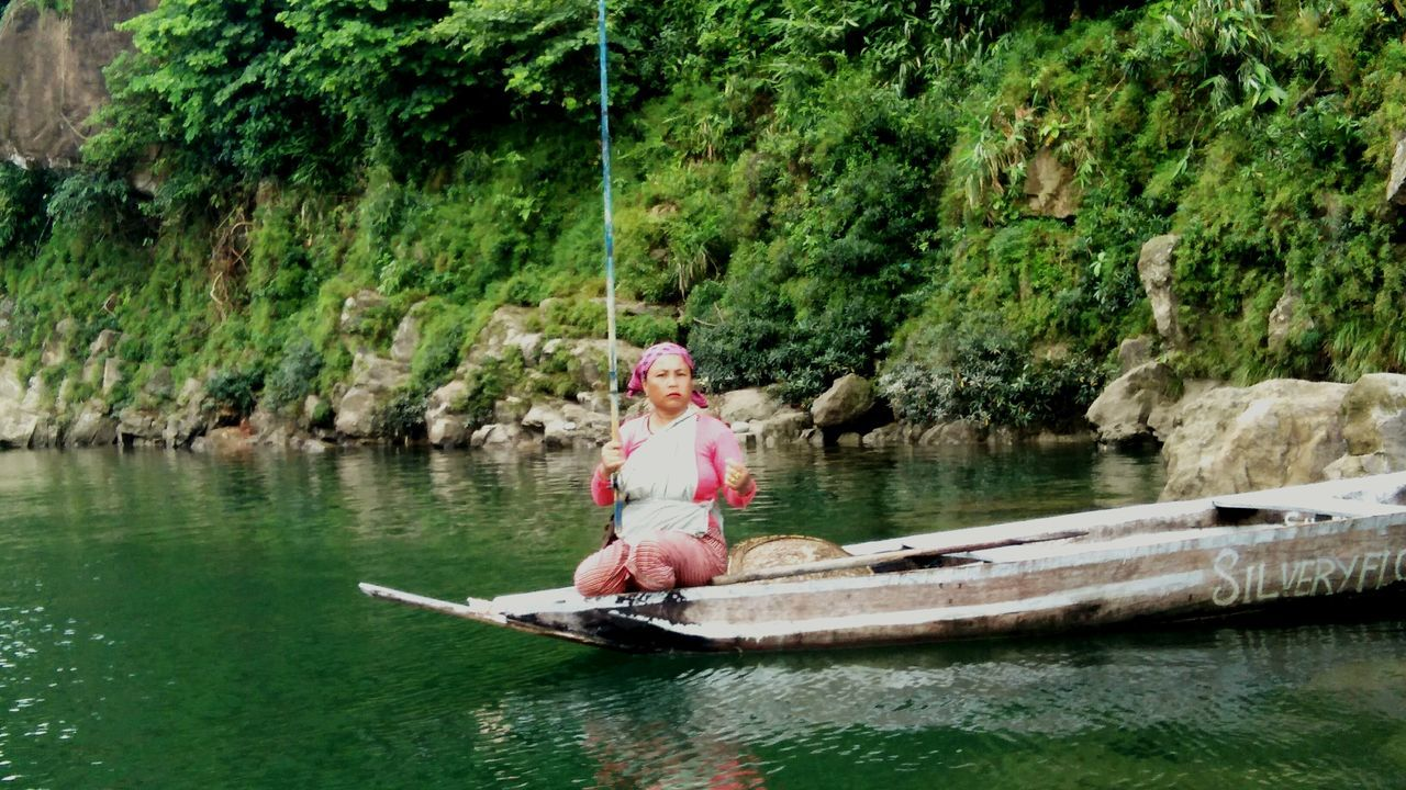 water, river, tree, waterfront, nautical vessel, real people, oar, one person, day, outdoors, nature, leisure activity, rock - object, transportation, sitting, sailing, full length, beauty in nature, lifestyles, men, scenics, rowing, adult, people