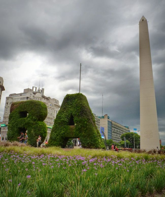 Obelisco Buenos Aires. City Cityscape Outdoors Day Travel Destinations Architecture Social Issues Cultures History Sky Dramatic Sky Storm Cloud Grass Garden Flowers Buenos Aires Emblematic Places