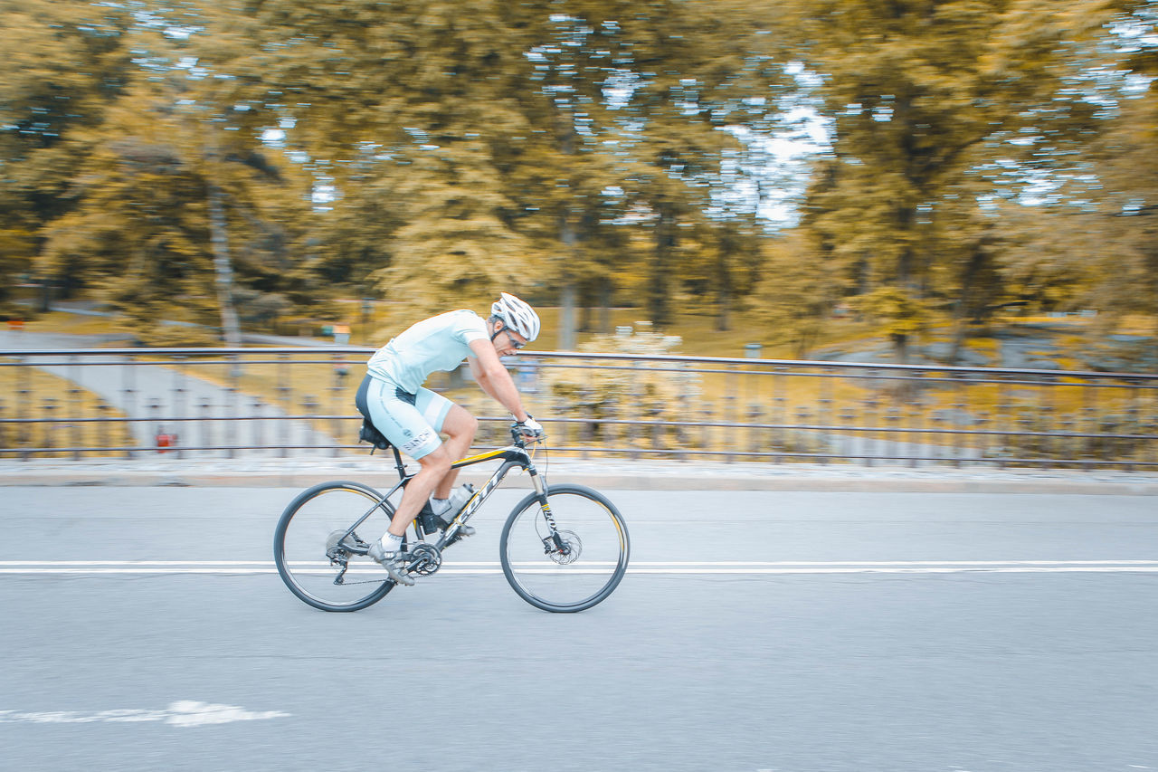 Athlete Bicycle Competition Competitive Sport Cycling Cycling Helmet Endurance Exercising Headwear Healthy Lifestyle Helmet Lifestyles Men Motion One Person Outdoors Racing Bicycle Riding Speed Sport Sports Clothing Sports Race Sportsman Transportation Tree
