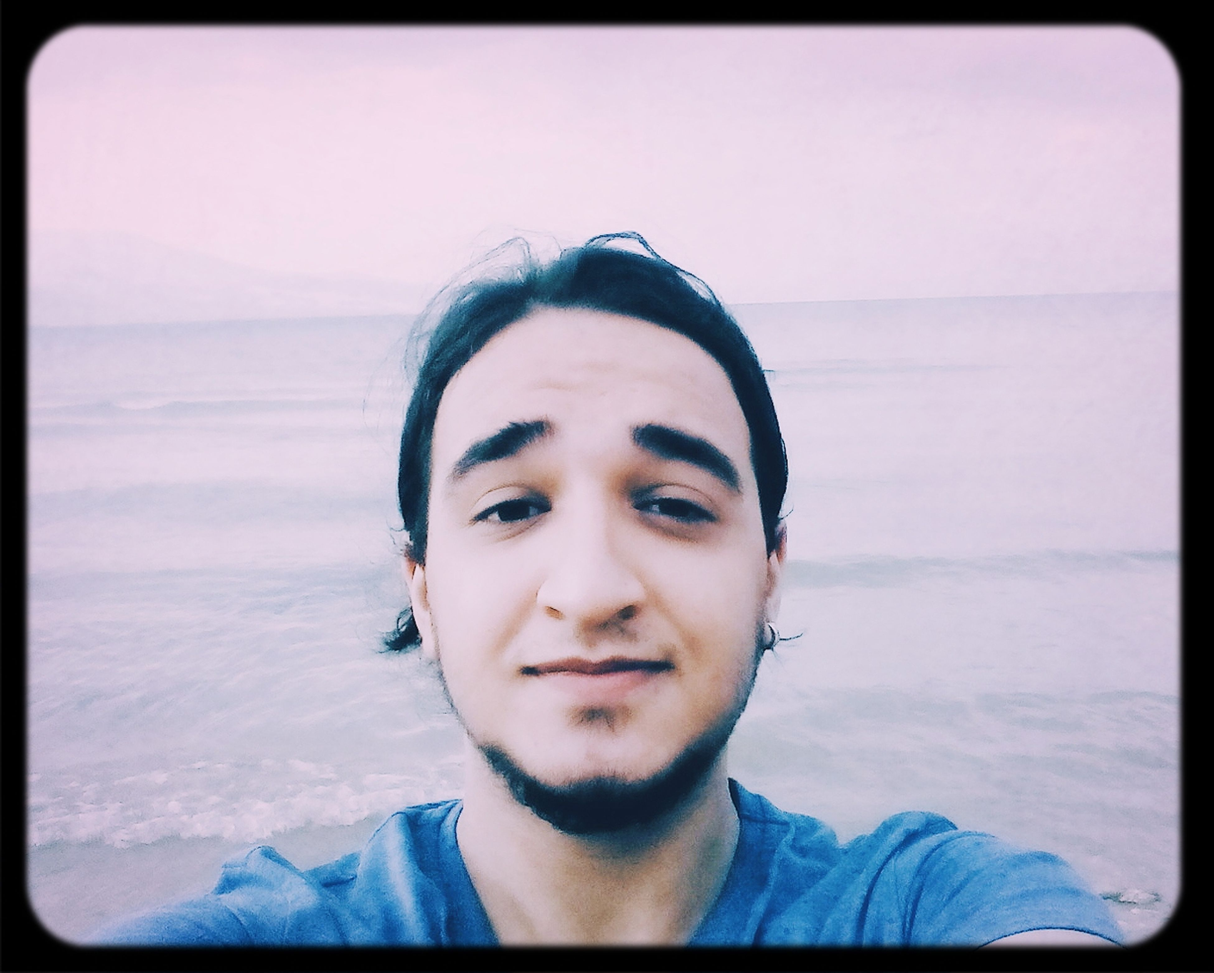 sea, beach, water, portrait, looking at camera, transfer print, auto post production filter, shore, lifestyles, young adult, headshot, person, leisure activity, young men, horizon over water, sand, front view, tranquility