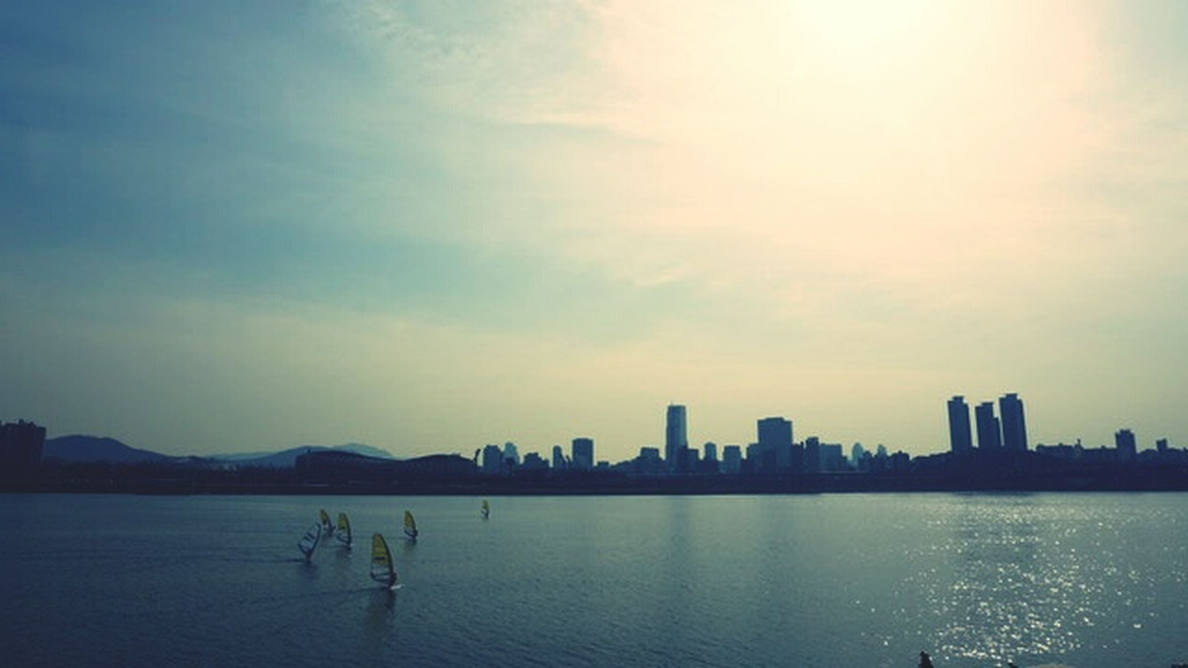 water, building exterior, silhouette, architecture, built structure, sky, city, sea, waterfront, sunset, cityscape, river, urban skyline, cloud - sky, city life, lifestyles, leisure activity, skyscraper, men