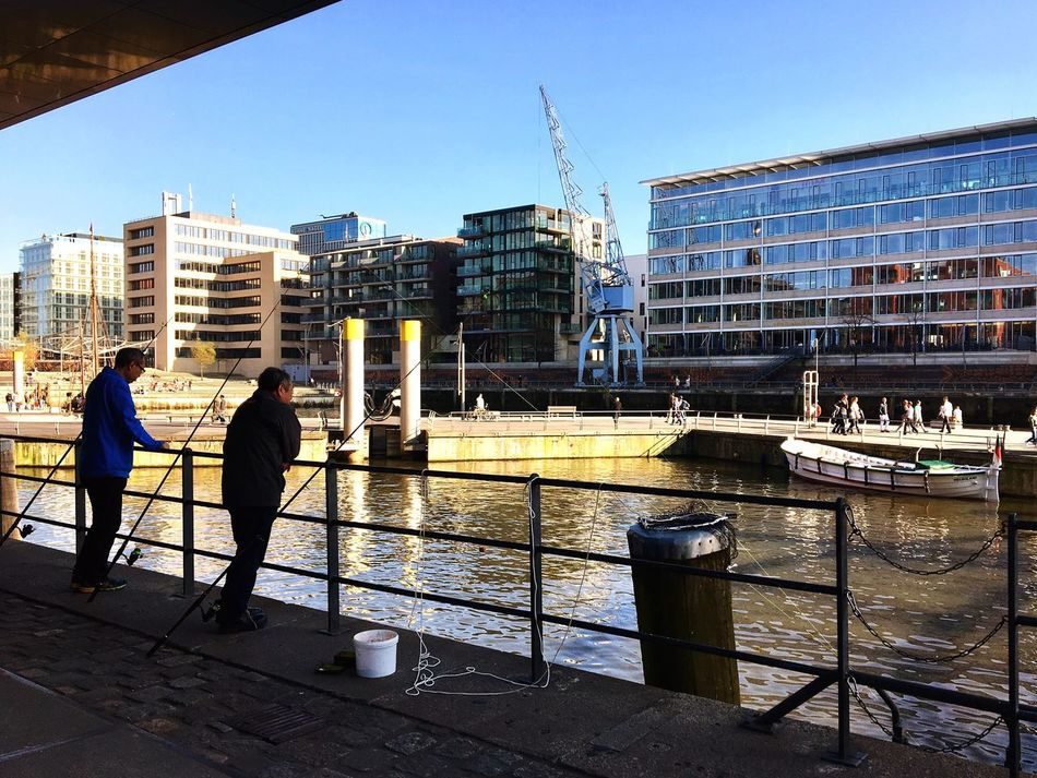 Two sites of the coin. Crowd on one and contemplation on the other. Contemplating Fishing City Life Sunday Afternoon Leisure Springtime Hamburg Hamburg Hafencity Urban Streetphotography Men Sunday Fishing Time Fishing Life Friends Friendship Light And Shadow