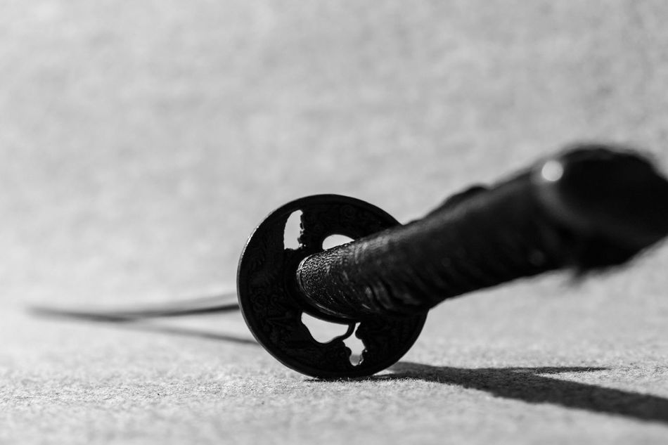 Black and white shot of one Japanese sword, katana, on the floor with simple textured out of focus background and selective focus. Art Artistic Arty Black And White Bokeh Close-up Cloth Equipment Fight Floor Ground Hard Shadows Indoors  Japan Japanese  Katana Martial Arts Material Metal No People Samurai Selective Focus Sharp Sword Texture