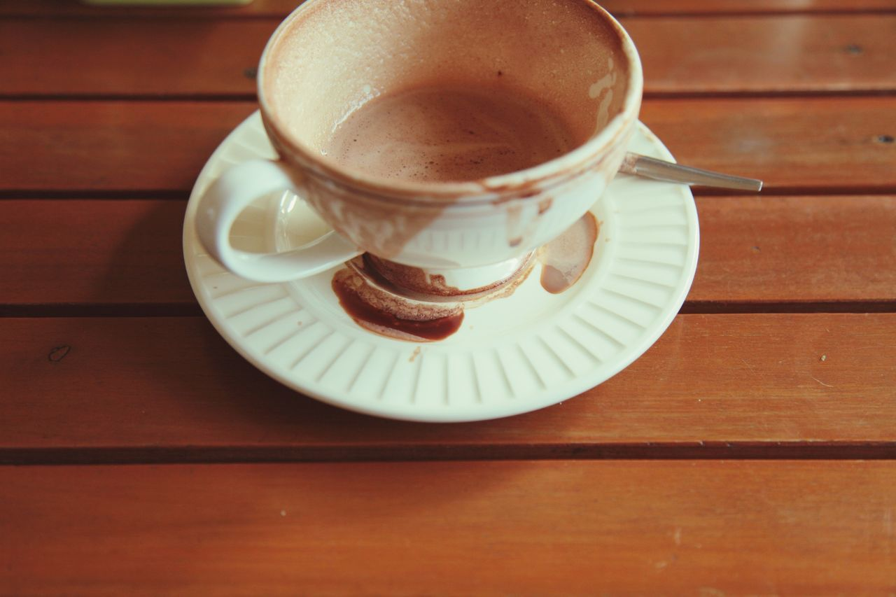 High Angle View Of Messy Coffee Cup On Wooden Table