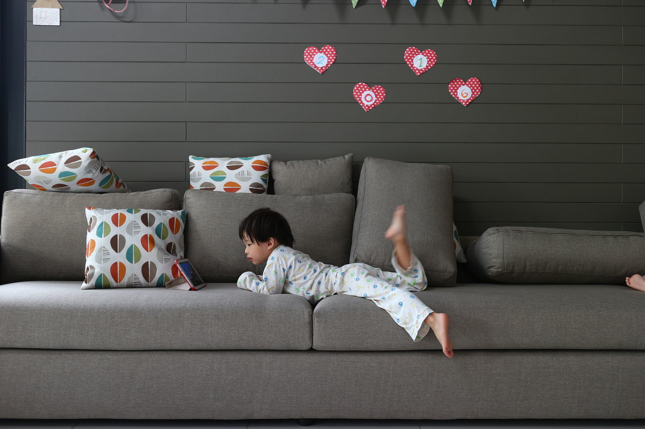 Side View Of Boy Using Digital Tablet While Lying On Sofa At Home